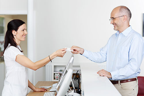 Woman at front desk handing a credit card back to a patient