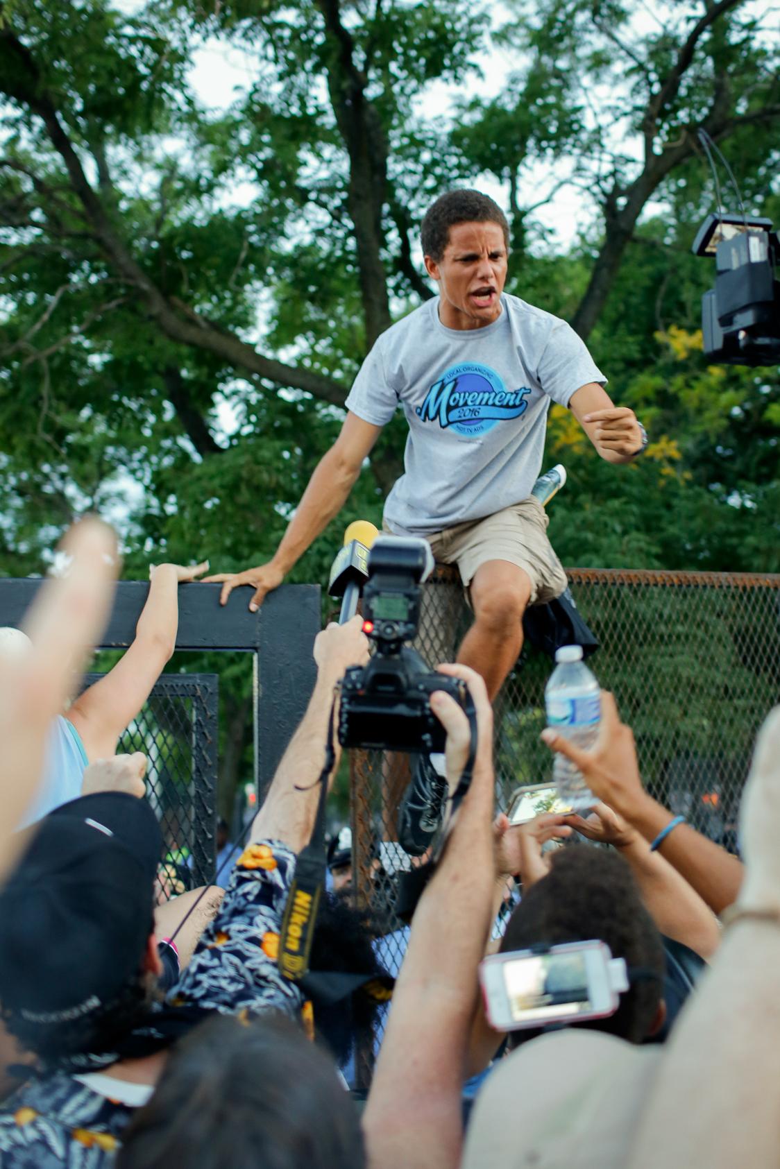 Demonstrator Climbs Barricade at 2016 DNC