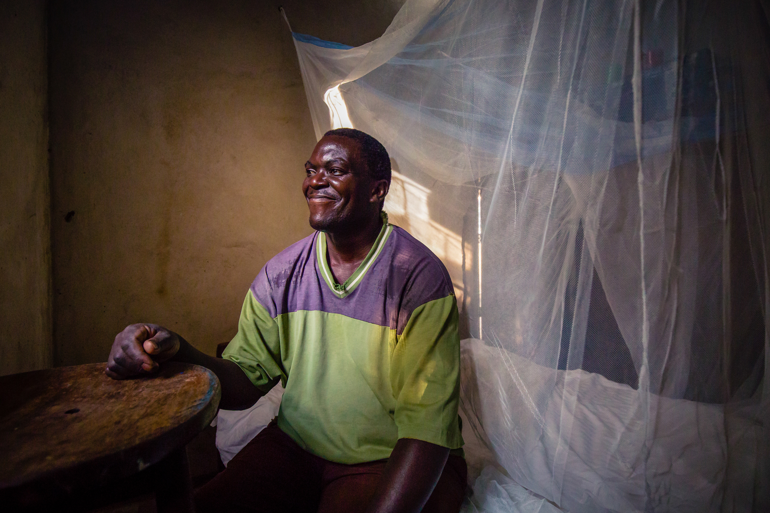 This is Timothy, a Ugandan living in a rural village near Namungalwe, Iganga District, Uganda. In all of Uganda, malaria is a constant risk, but especially so in the villages.  Here, Timothy displays his mosquito net, the first line of defense against malaria, which was provided by the Uganda Village Project. Taken in Iganga District, Uganda. July 2018. Photo by Ben Blankenship.