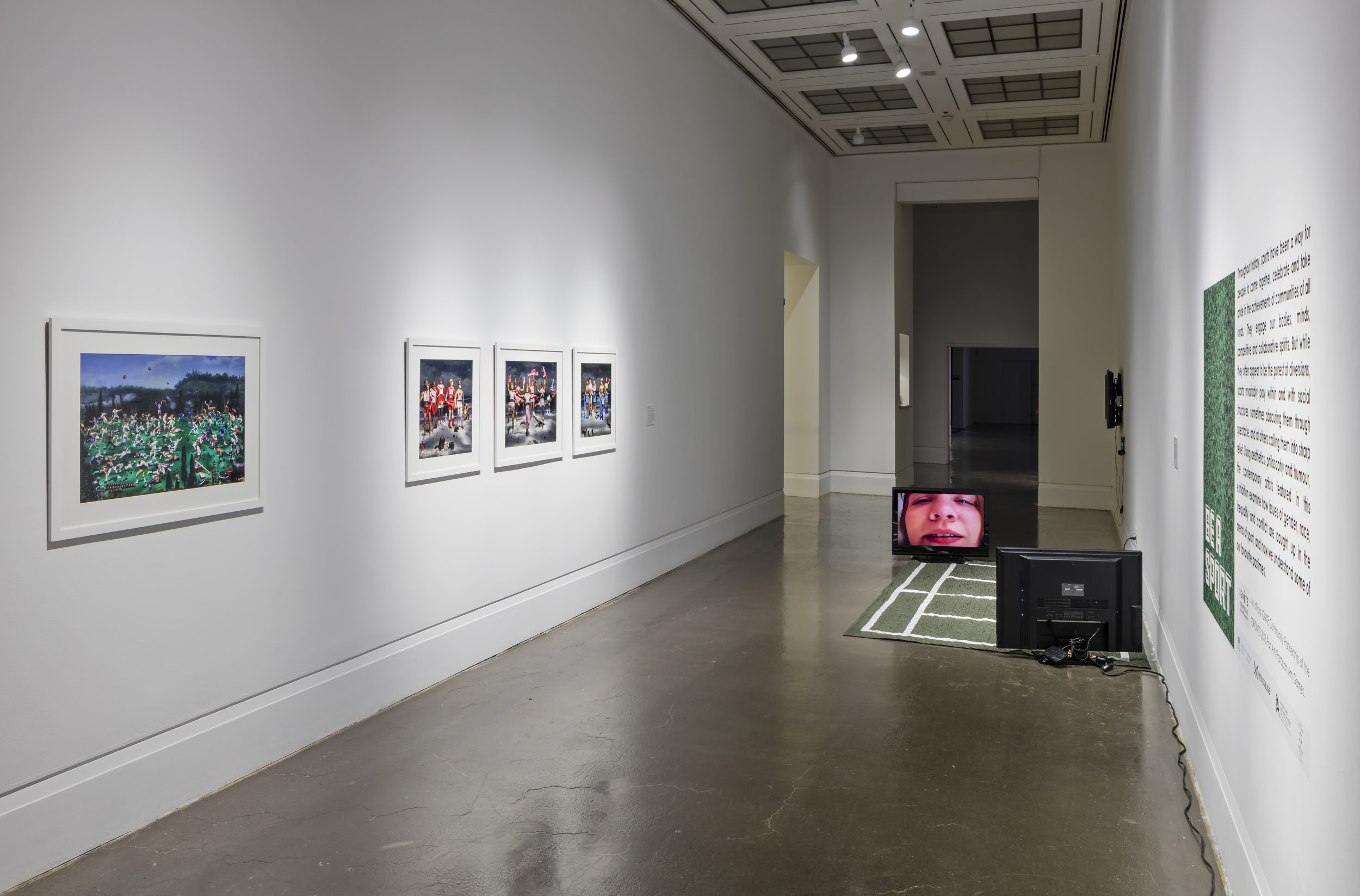 Be A Sport , Robert Freeman Gallery, Art Gallery of Mississauga. Left: Diana Thorneycroft,  The Battle of Queenston Heights... , 2013,  NRA Sponsored Rhythmic Gymnastics Competition... , 2012. C-prints. Right: Weber & Schneider,  Wimbledom , 2000, Textile sculpture, two-channel video. Photo by Toni Hafkenscheid.