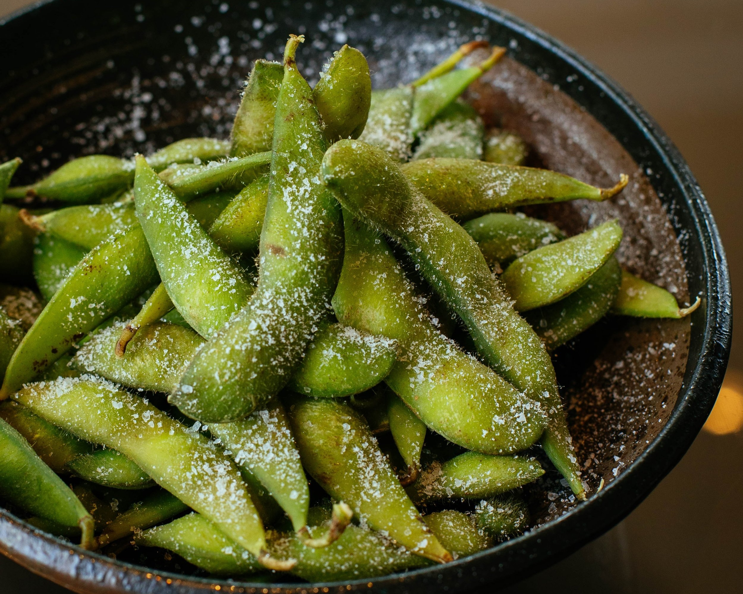 Lightly steamed edamame with or without salt is a delicious snack. Look for it in the freezer section of your grocery store.
