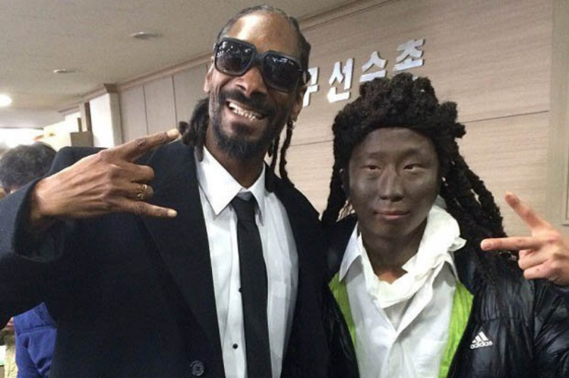 A South Korean fan dressed in blackface poses with Snoop Dogg in 2014.