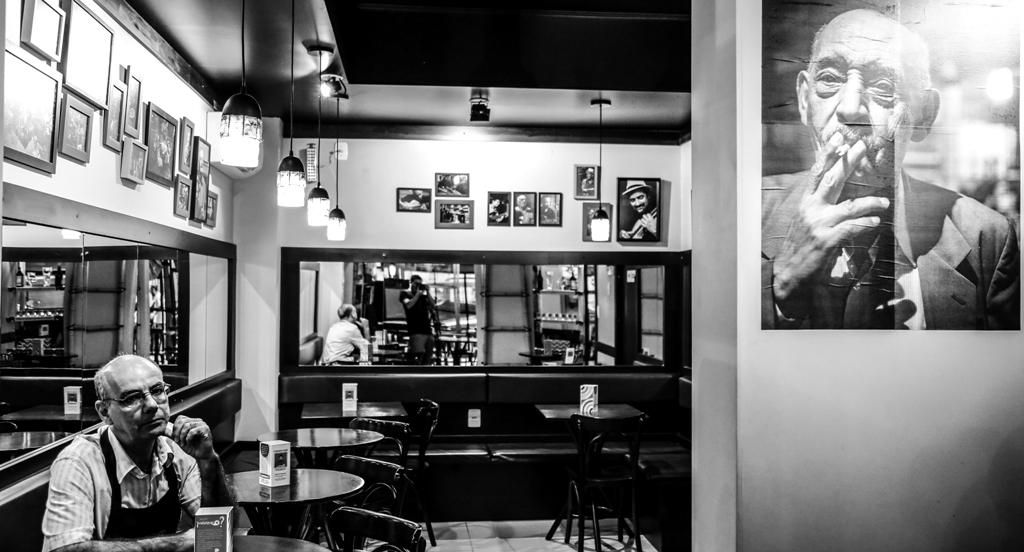 Seu Cláudio junto à imagem pendurada na parede do cantor e violonista Darcy Alves, o professor Darcy, que ajudou a popularizar o bar (Foto/Francisco Cadaval)