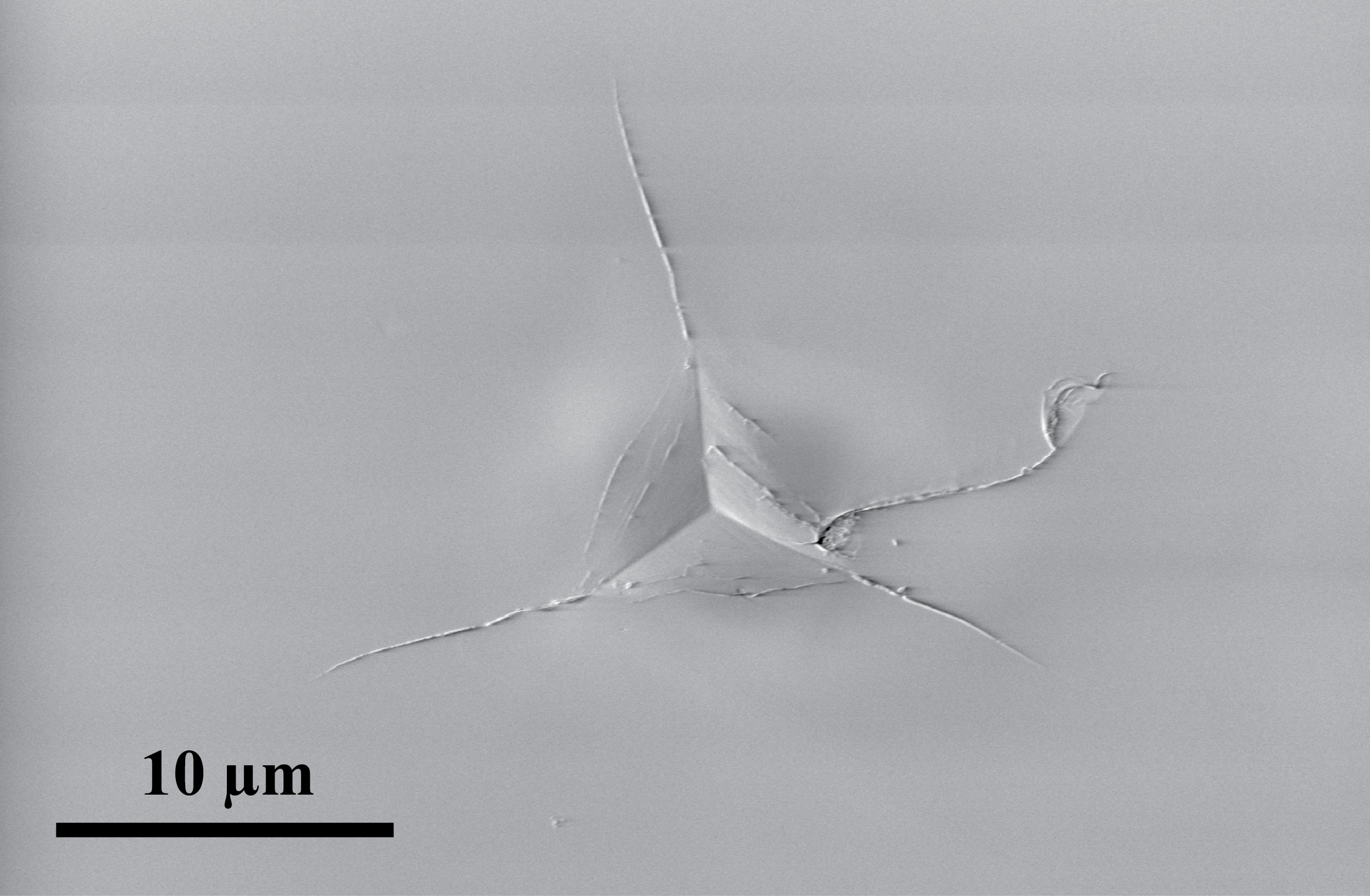 An example of a Berkovich (3-sided pyramid) indent in olivine. This secondary electron image was taken using a scanning electron microscope.