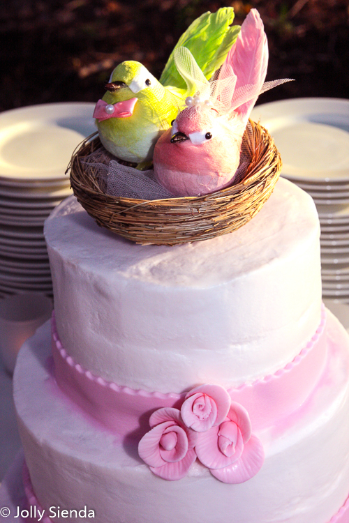 Pink and green lovebirds on a wedding cake
