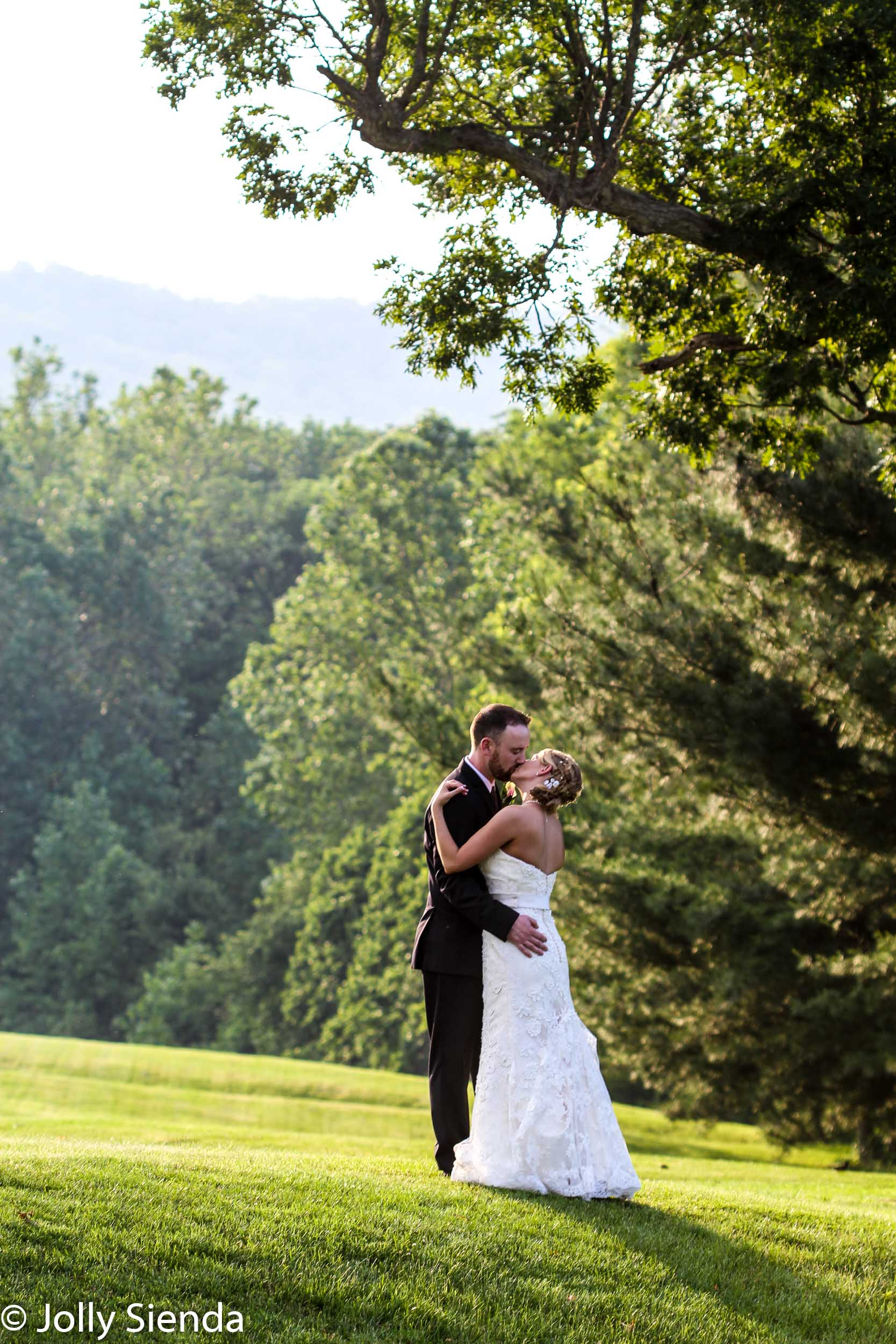 Portrait of a wedding couples kiss outside at a golf course unde