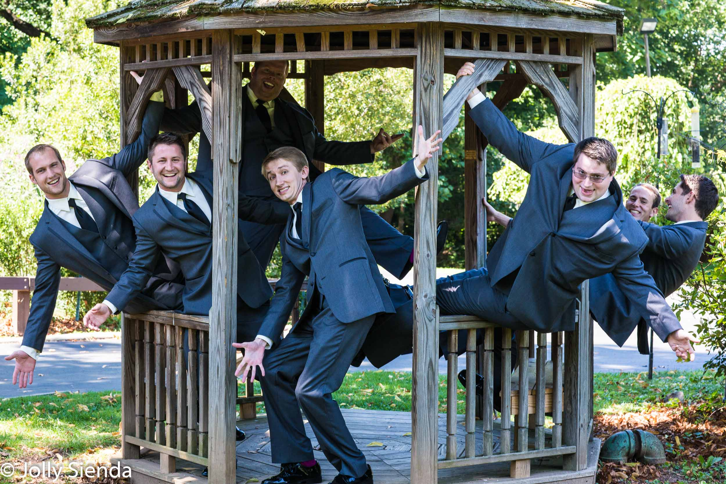 Groom, best man and groomsman hang out at the gazebo