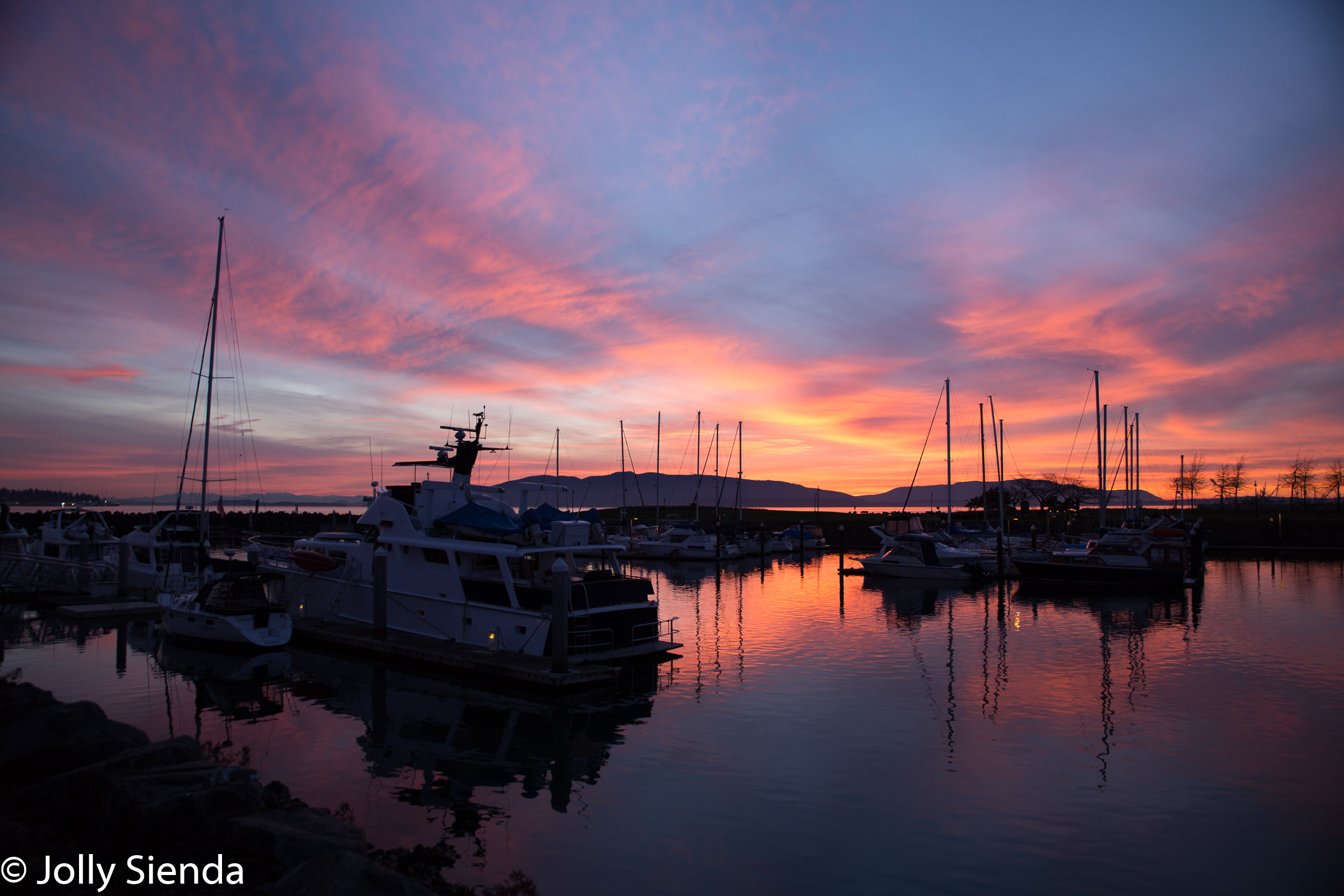 Pink sunset sets on a boat marina and Bellingham Bay