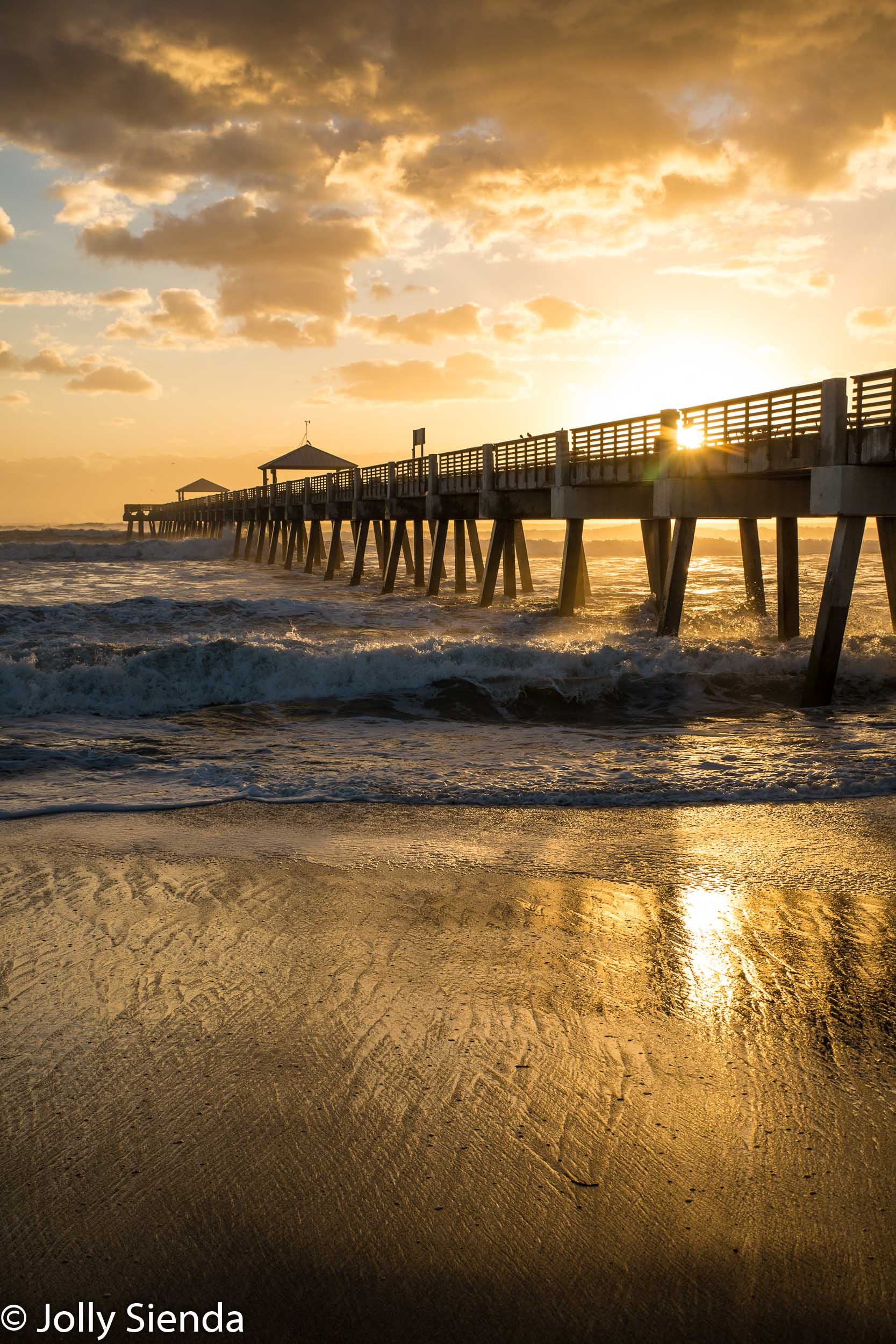 Sunburst and waves at the pier dock at Juno Beach