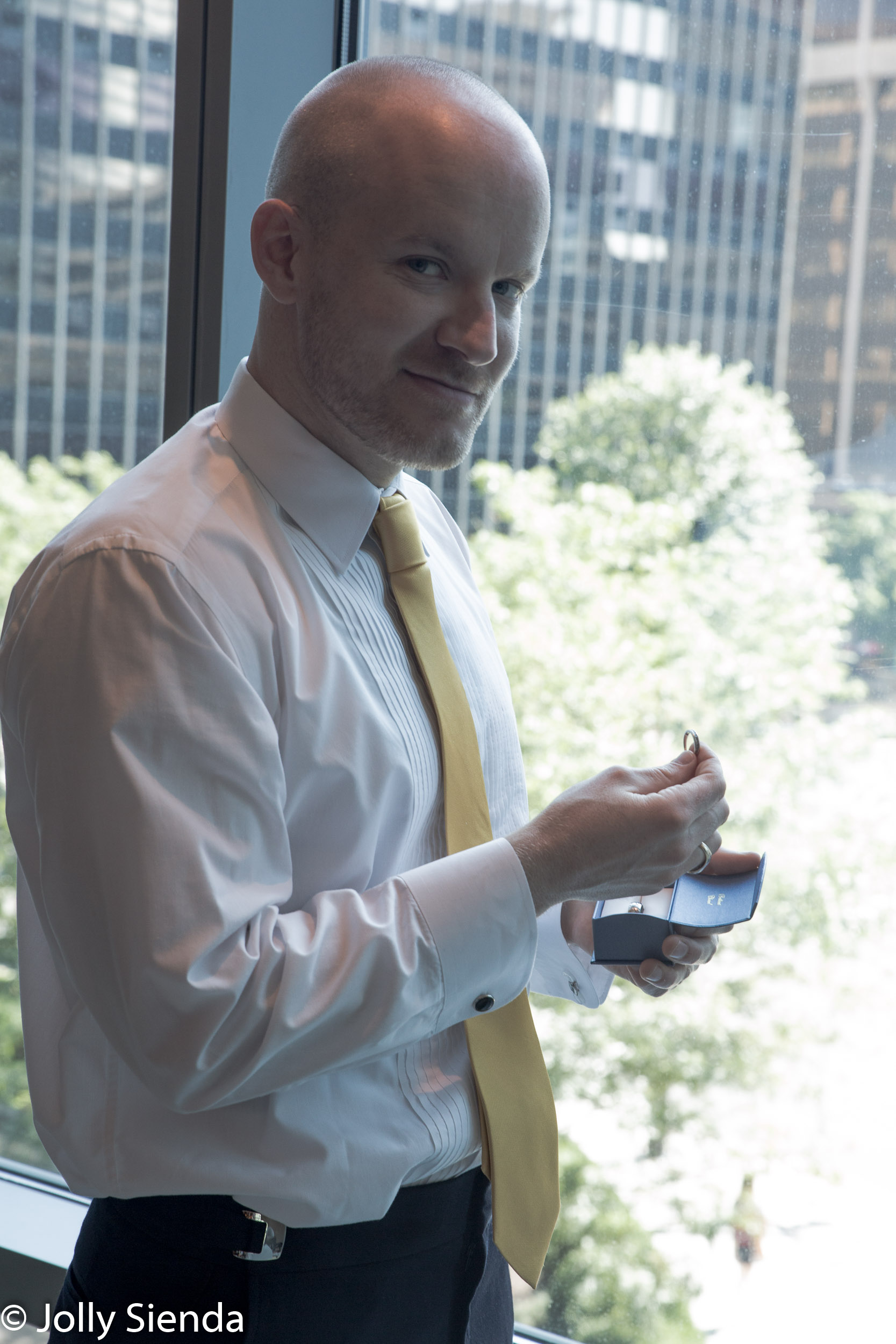 Portrait of a groom looking at the wedding rings