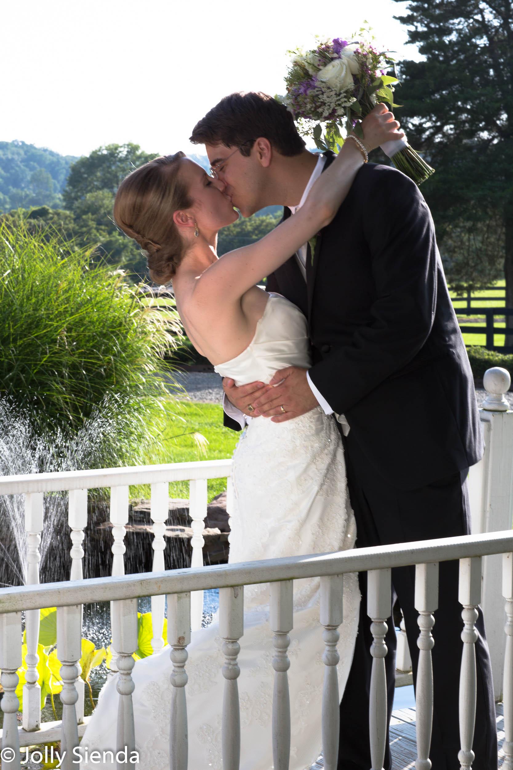 Groom kisses his bride on a bridge overlooking a pond - wedding