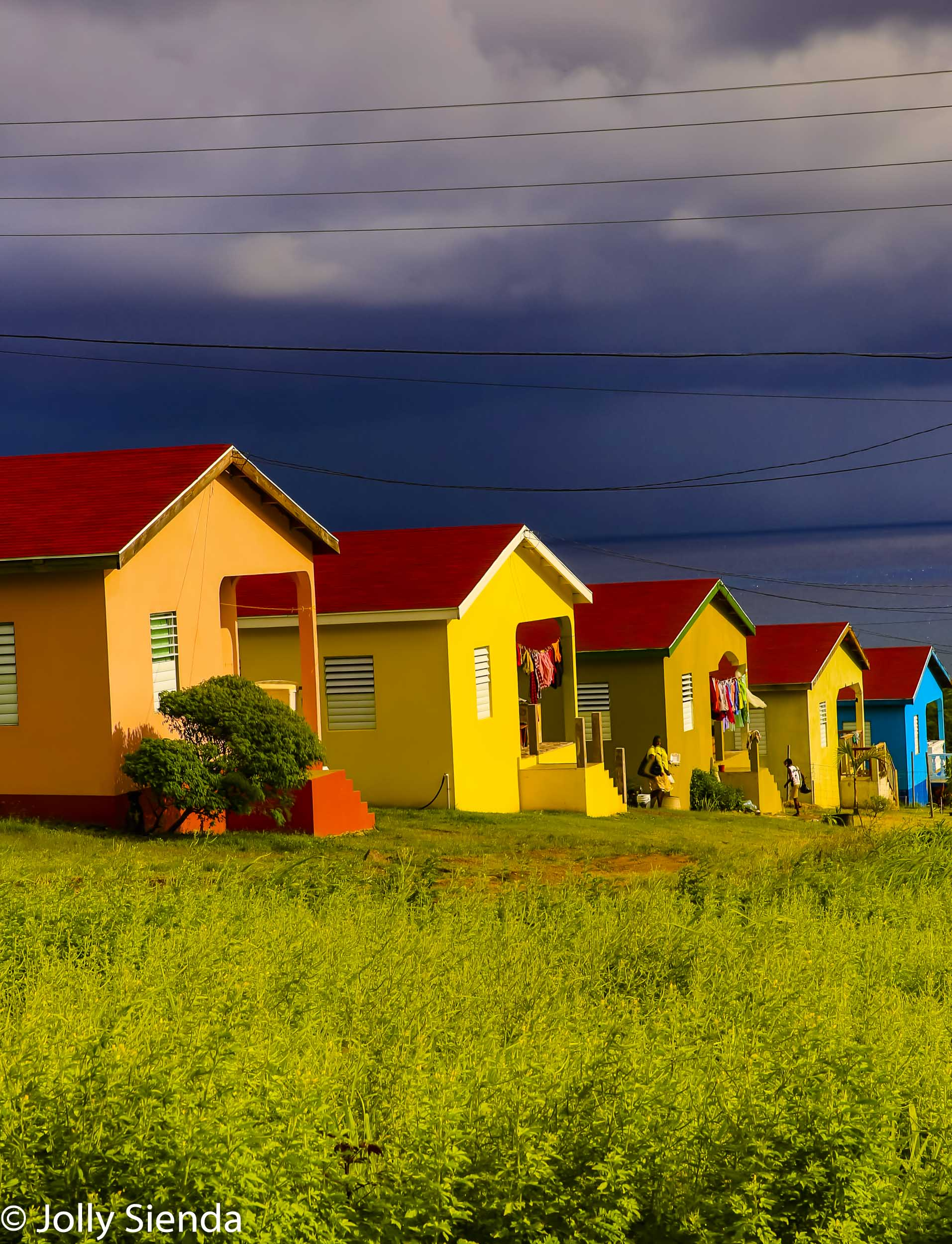 Colorful, Caribbean row houses, hanging laundry, meadow, people