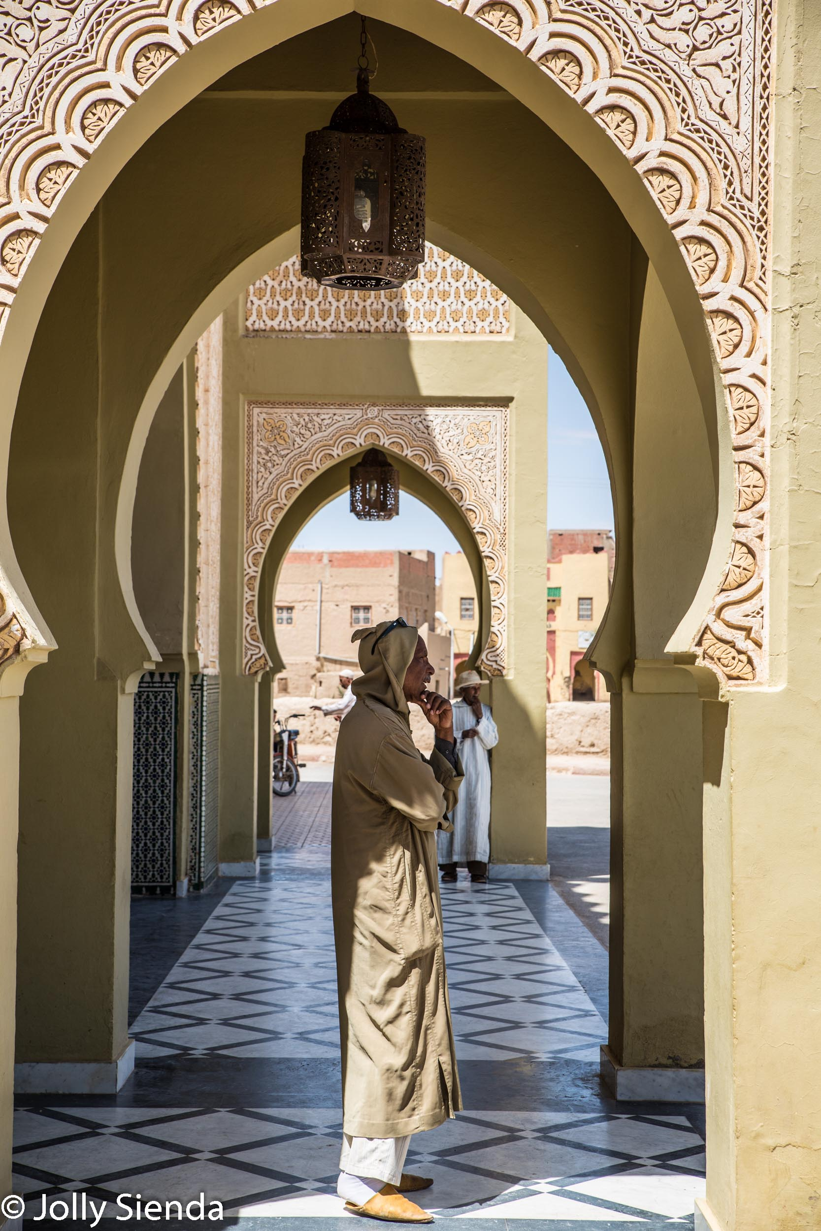 Man wears jalaba under islamic archway