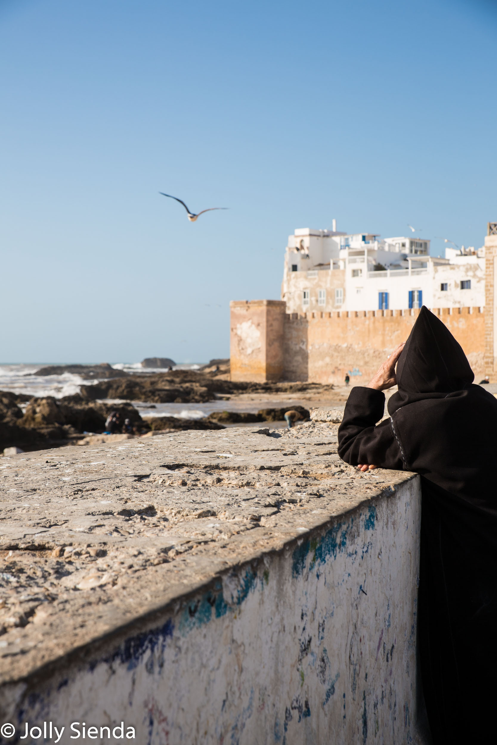Man wears jabala and looks at the sea at Essaouira