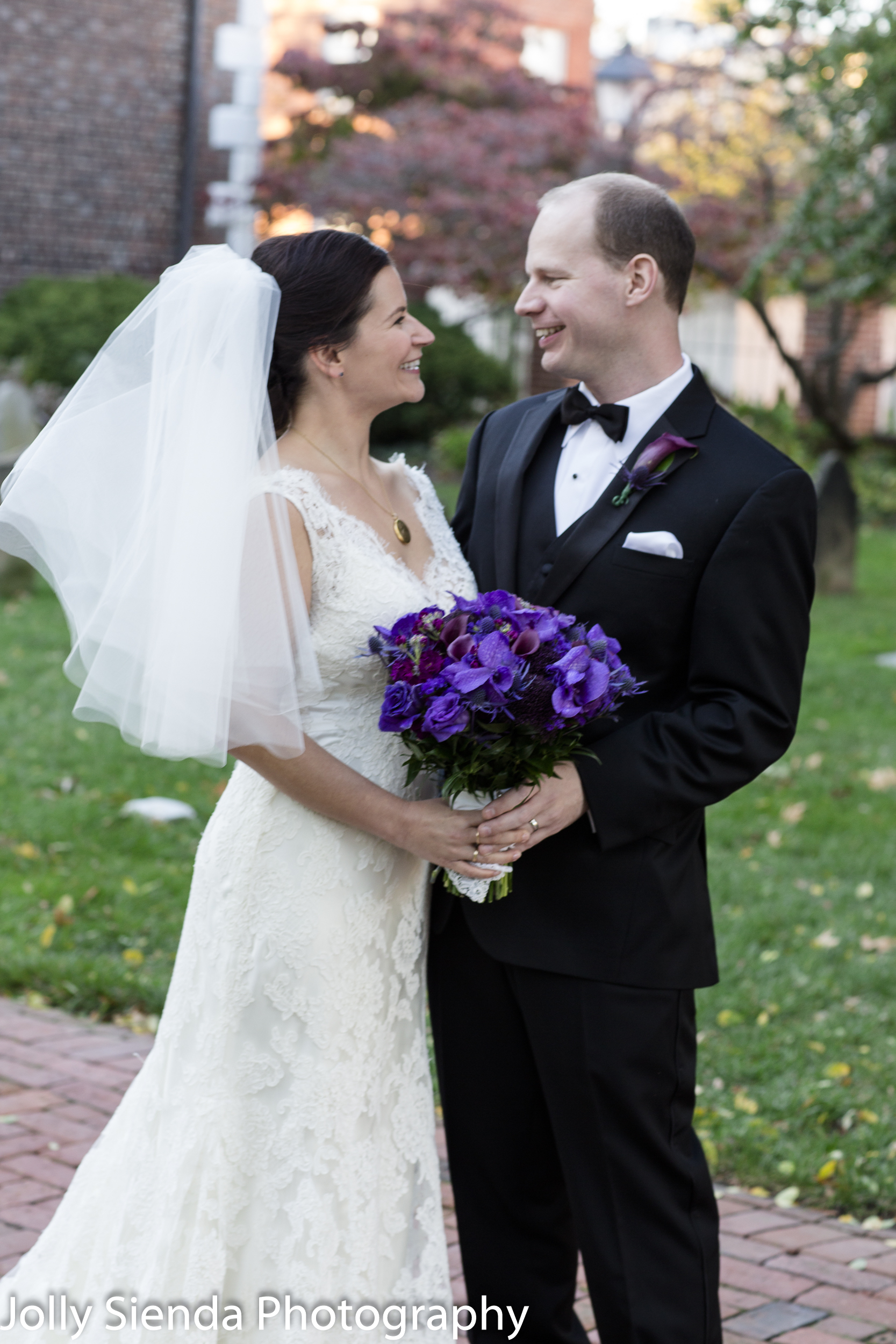 Purple wedding bouquet and the bride and groom
