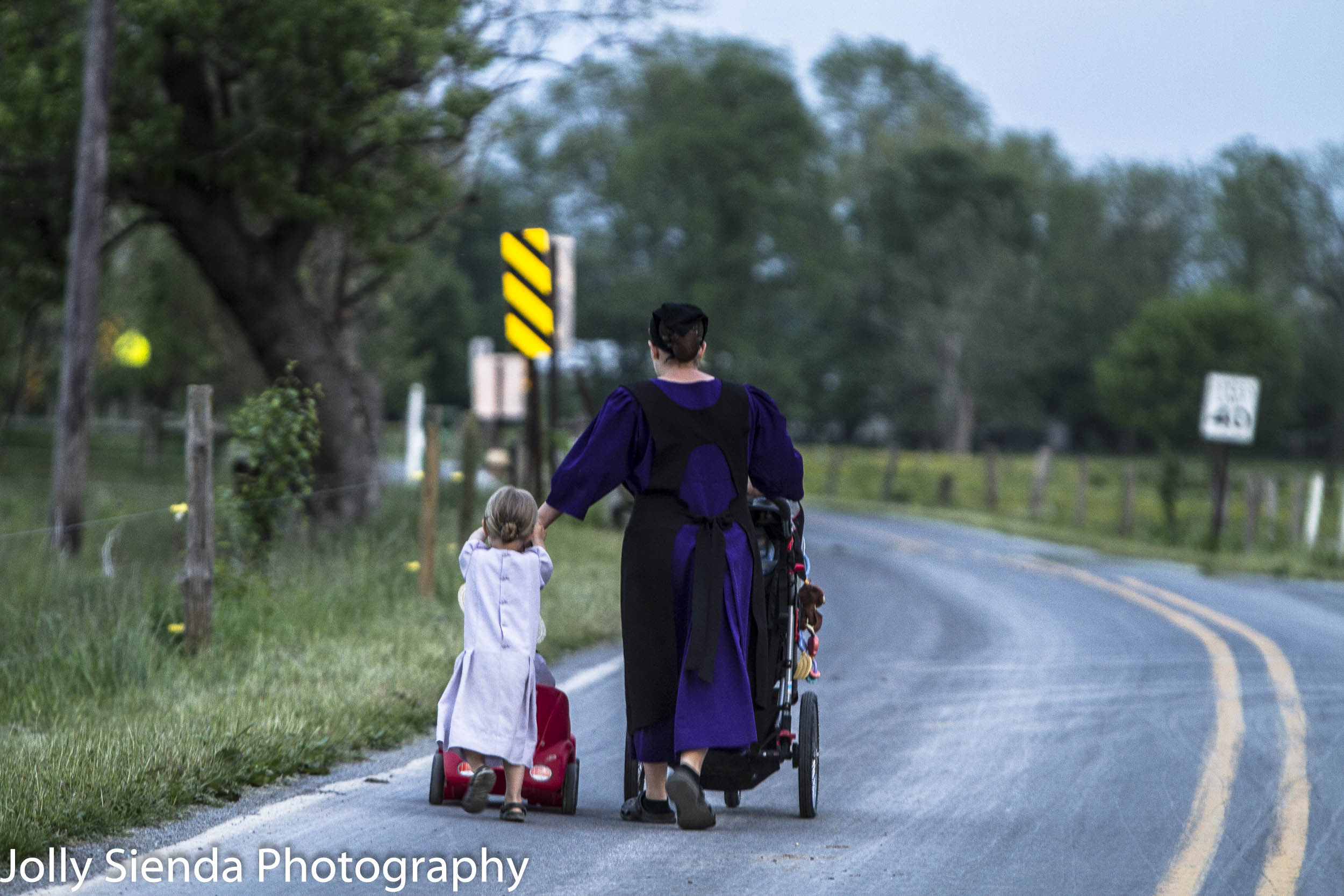 Amish mother pushes a baby carriage with her daughter