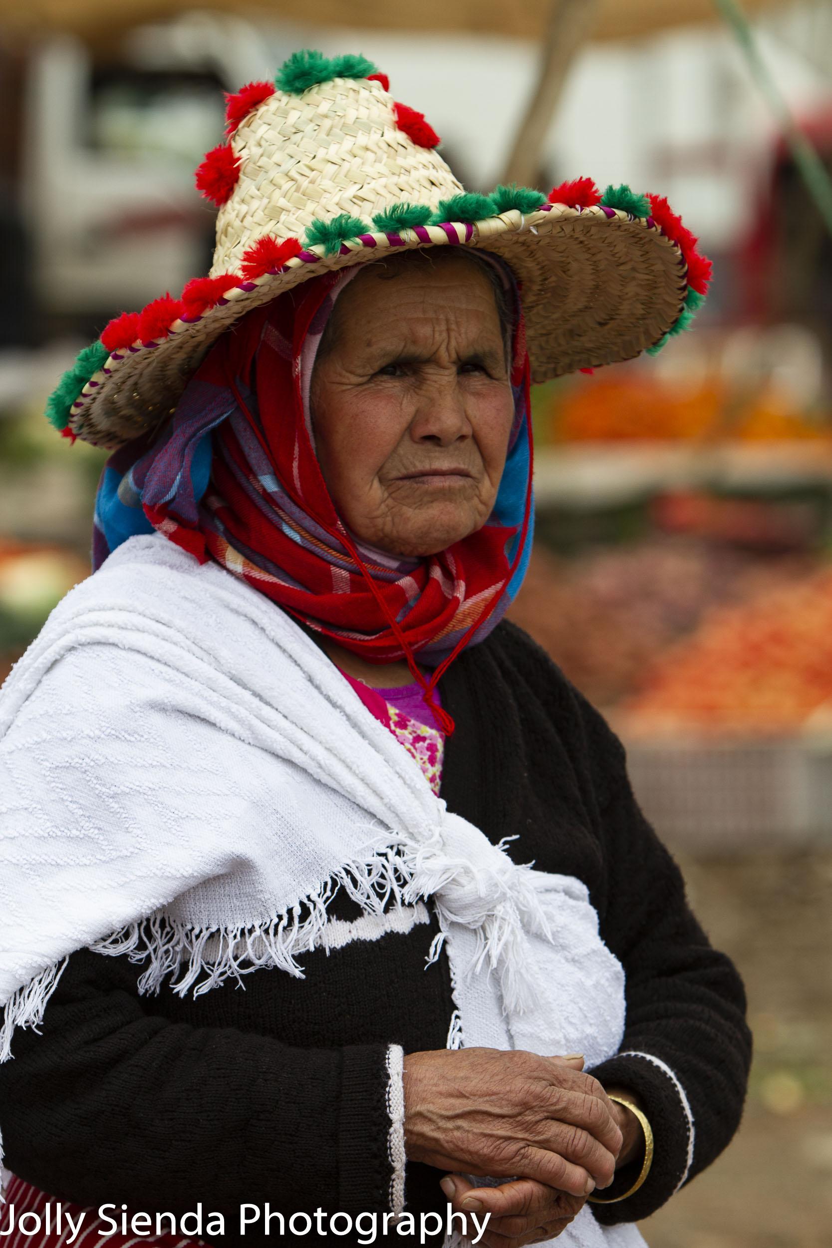 Old woman wears a Moroccan pom pom hat