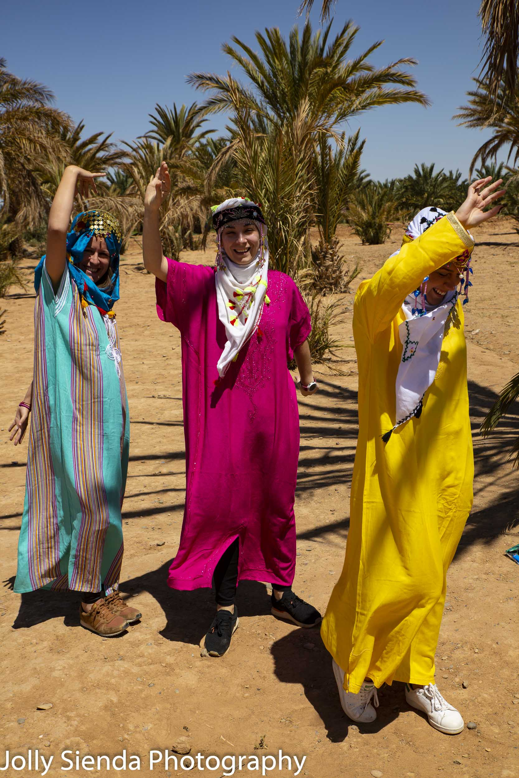 Female tourists dance and wear Moroccan caftens and head scarfs