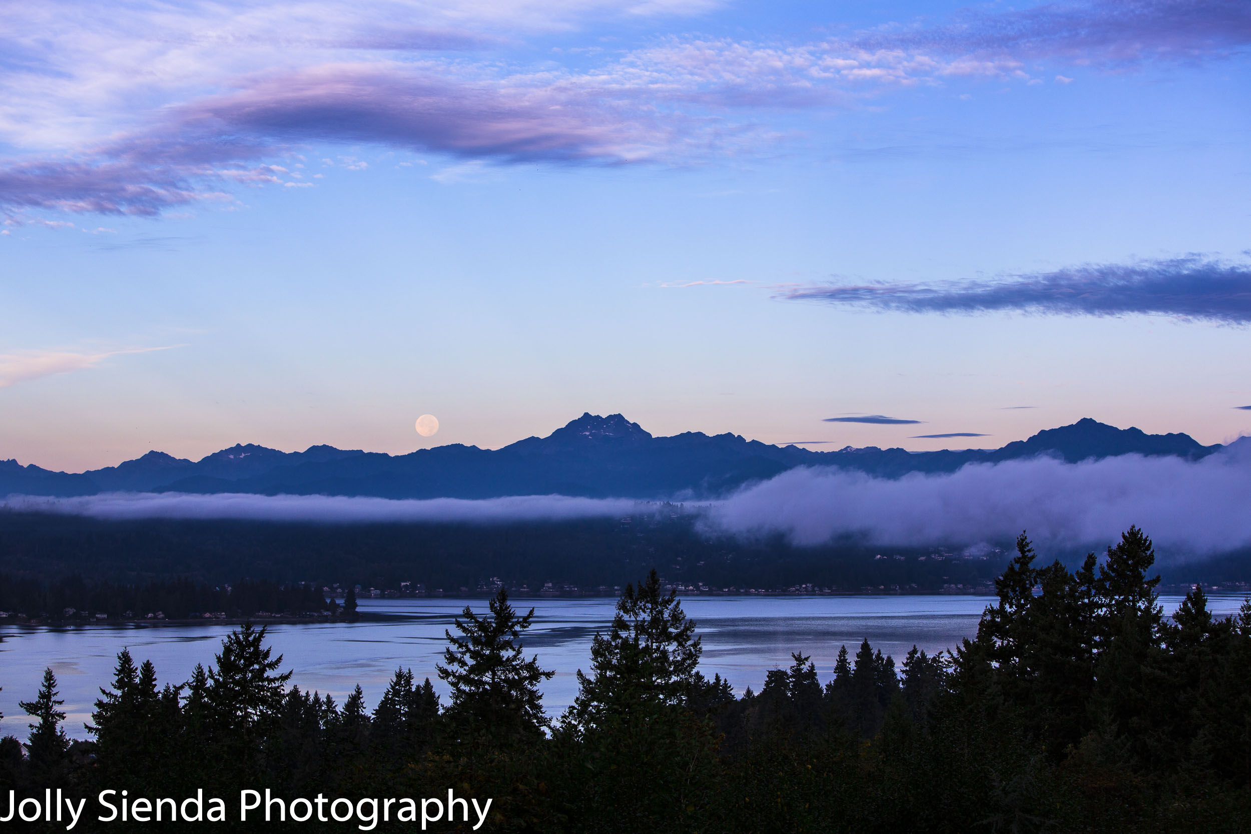 Autumn full moon over Olympic Mountains with fog rising over the