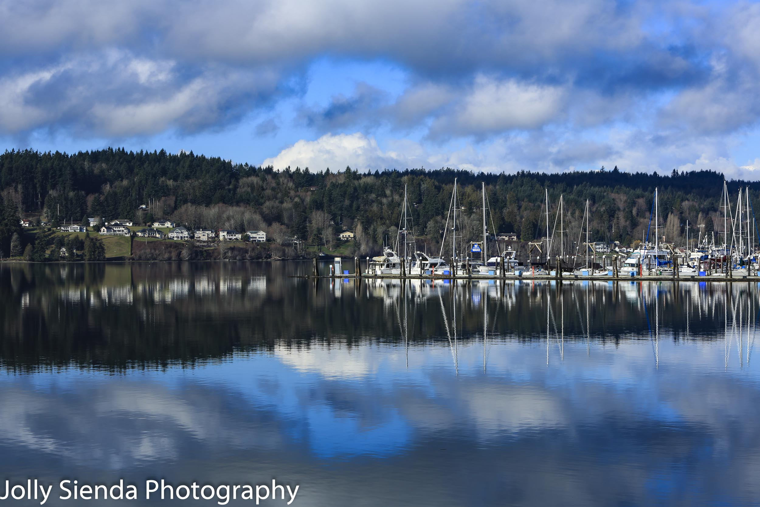 Reflection of clouds, waterfront, and boat marina on Liberty Bay