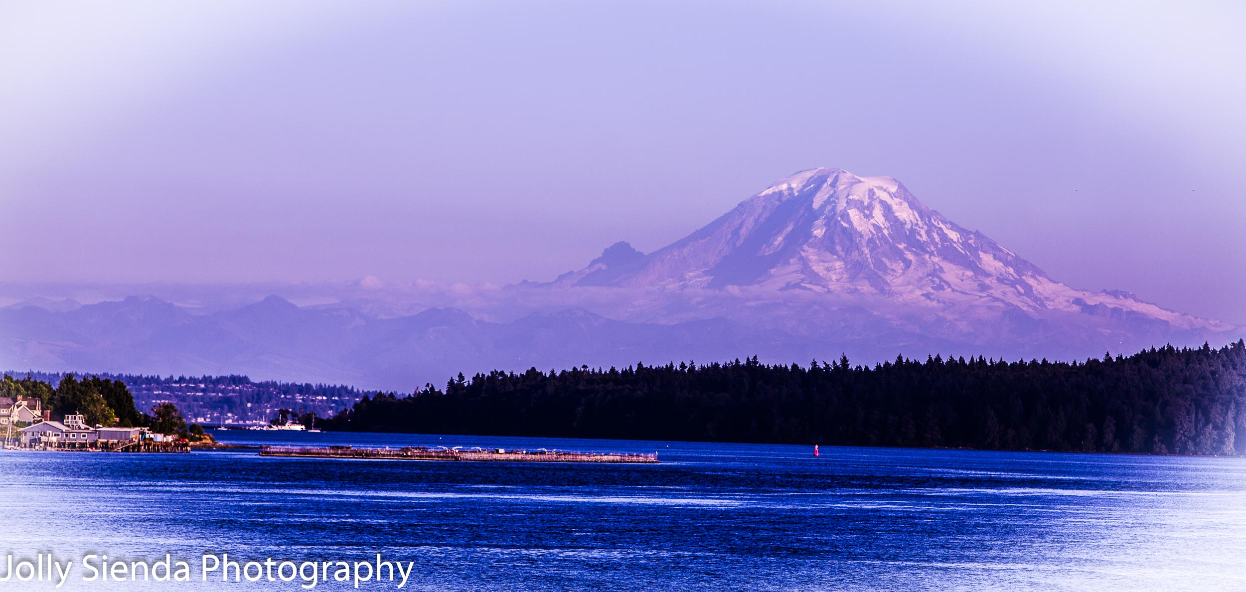 Mount Rainier at dusk towers over the Puget Sound during a pink