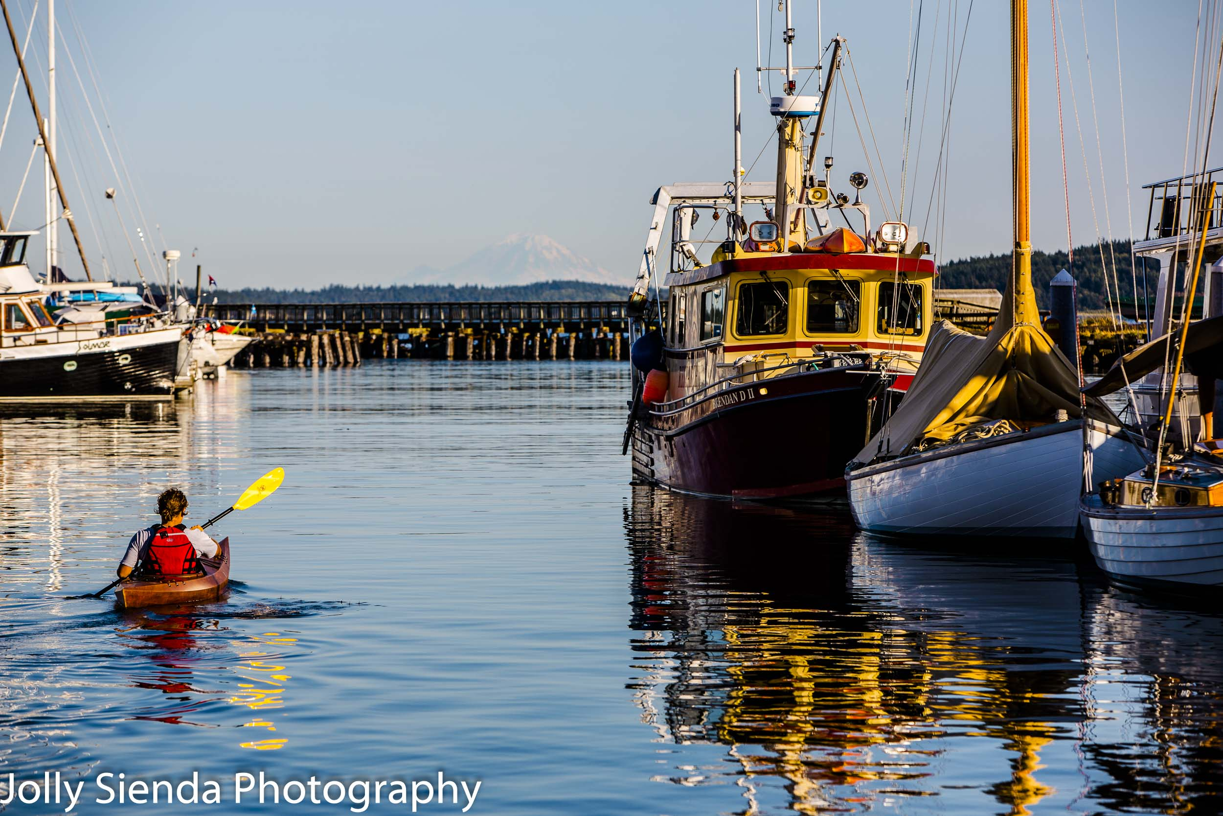Woman in a canoe on the Puget Sound passes boats and sailboats w