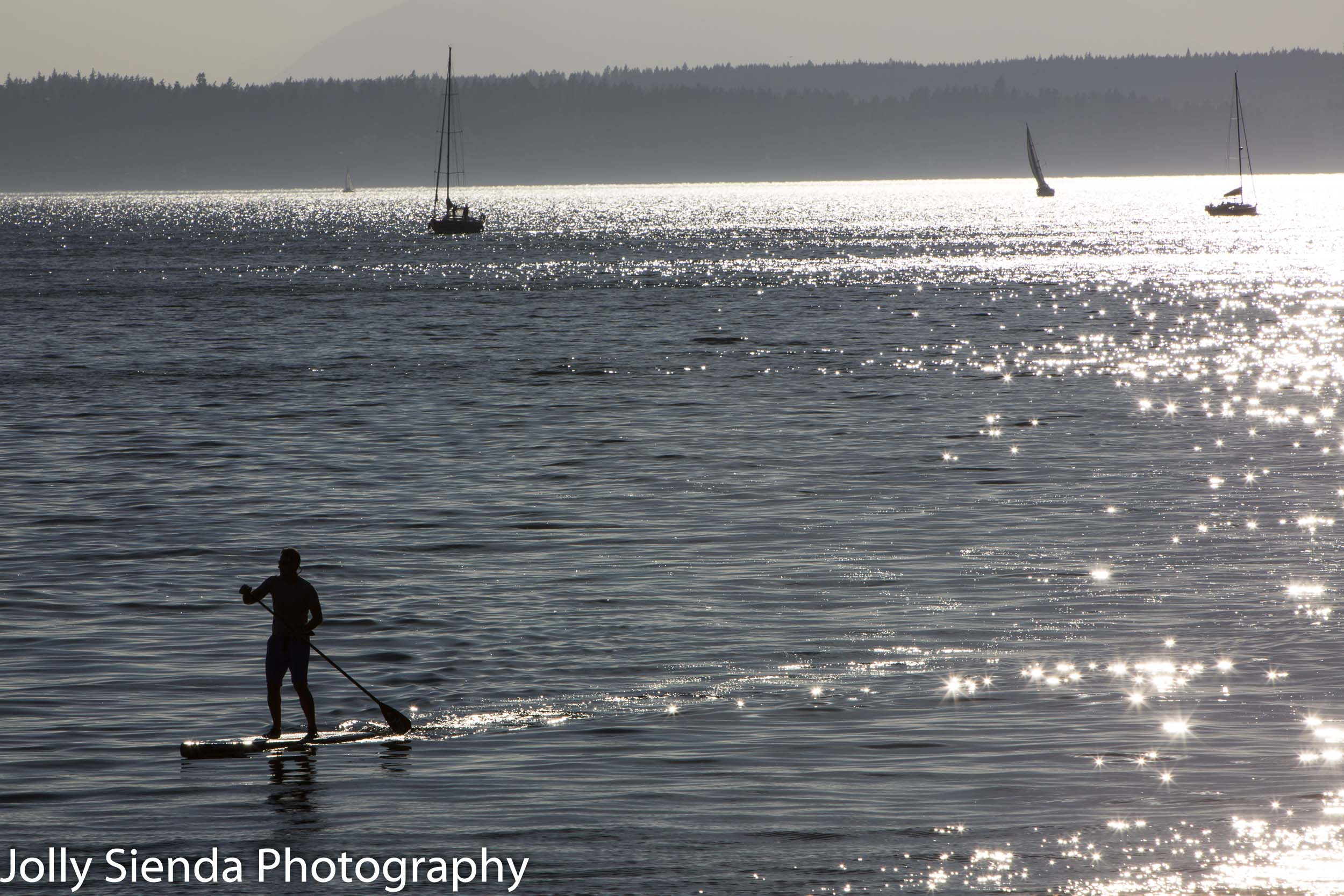 Paddle boarder and sailboats on the bay