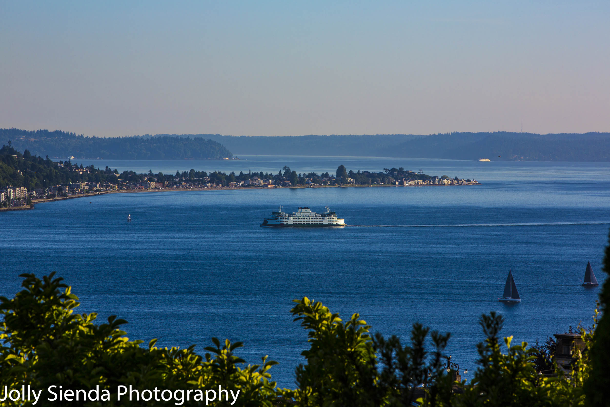 Ferry and sailboats on Elliott Bay passing West Seattle