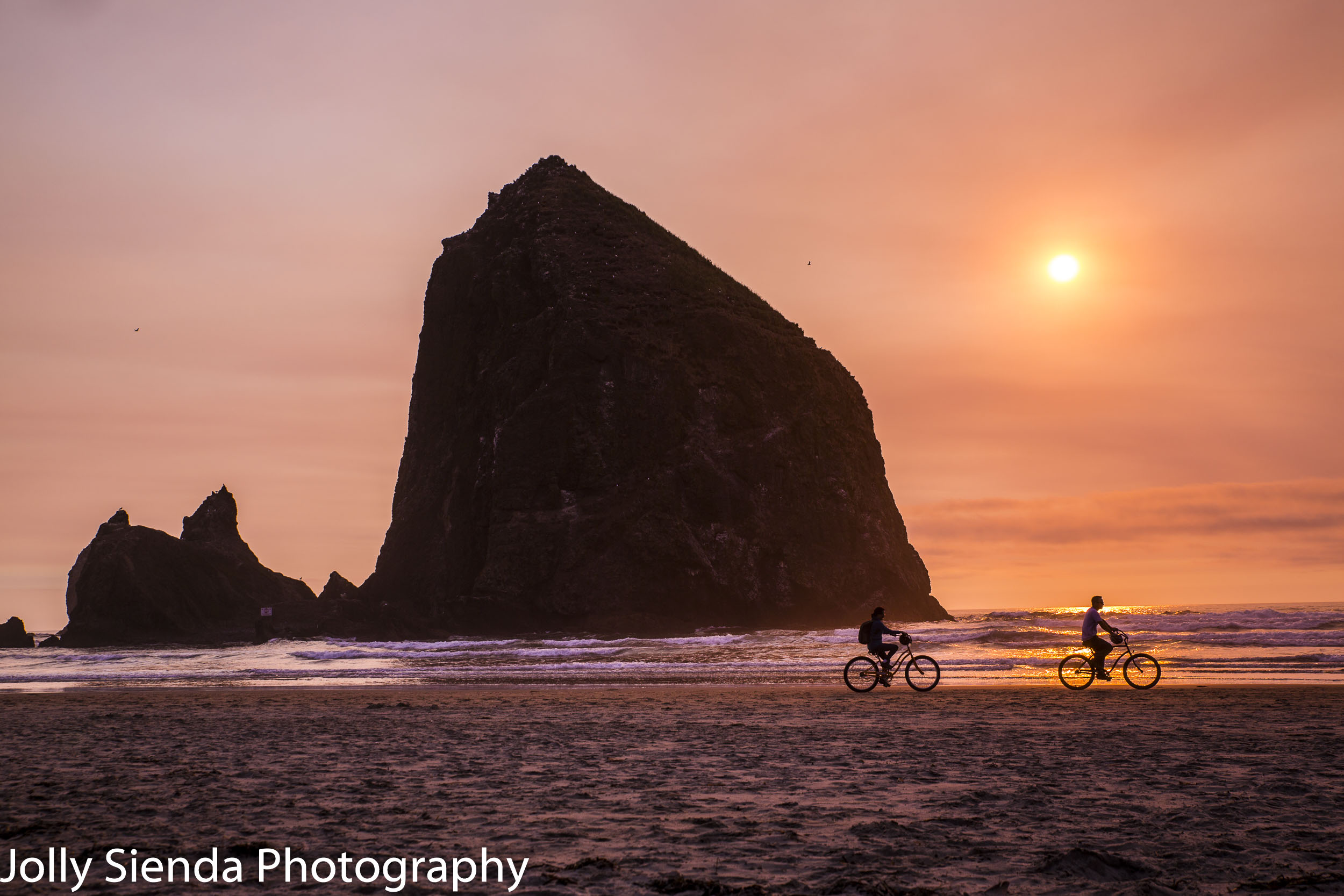 People ride bicycles past Haystack Rocks at sunset