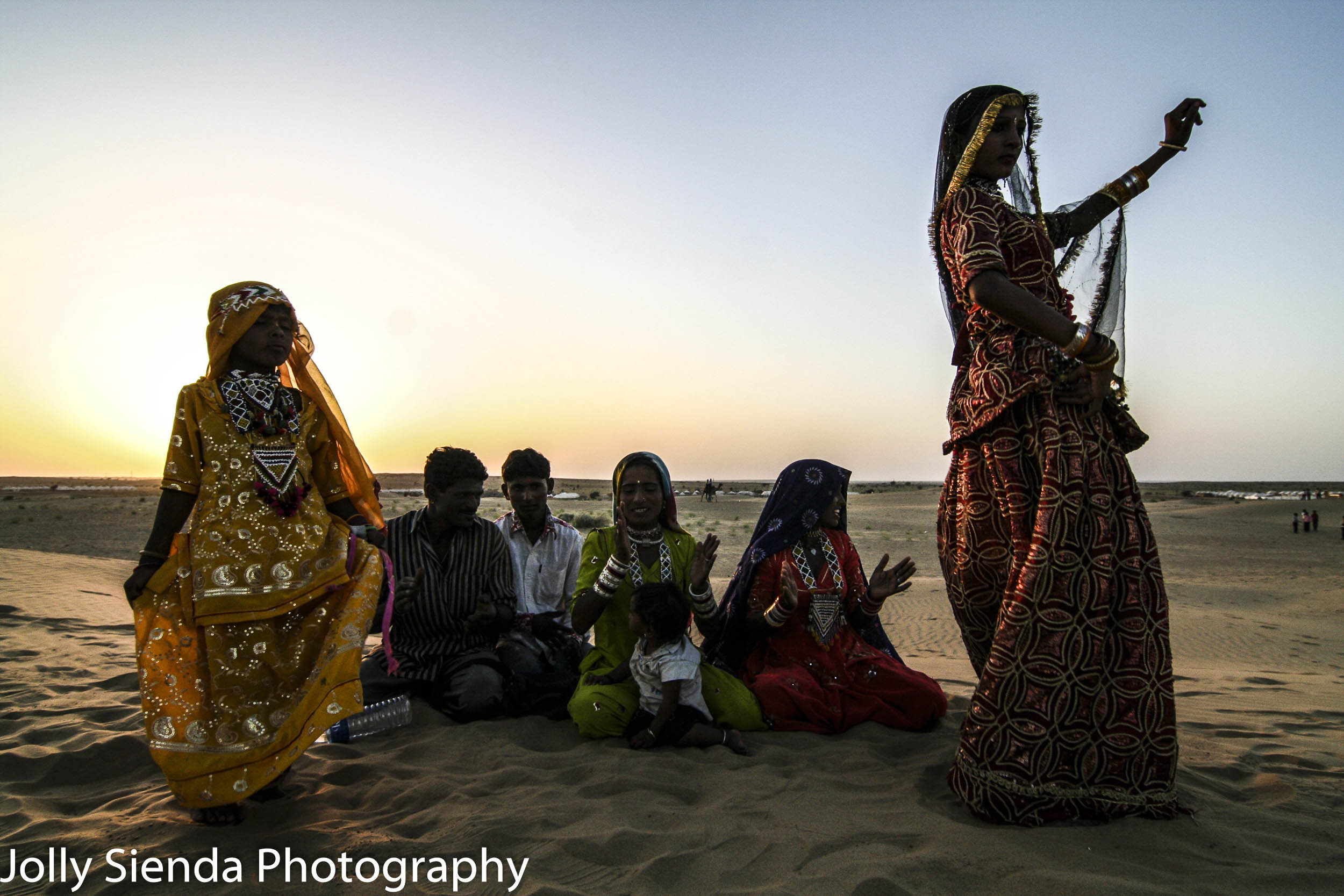Bedouin, banjaras woman and child dance on sand, in tradional co