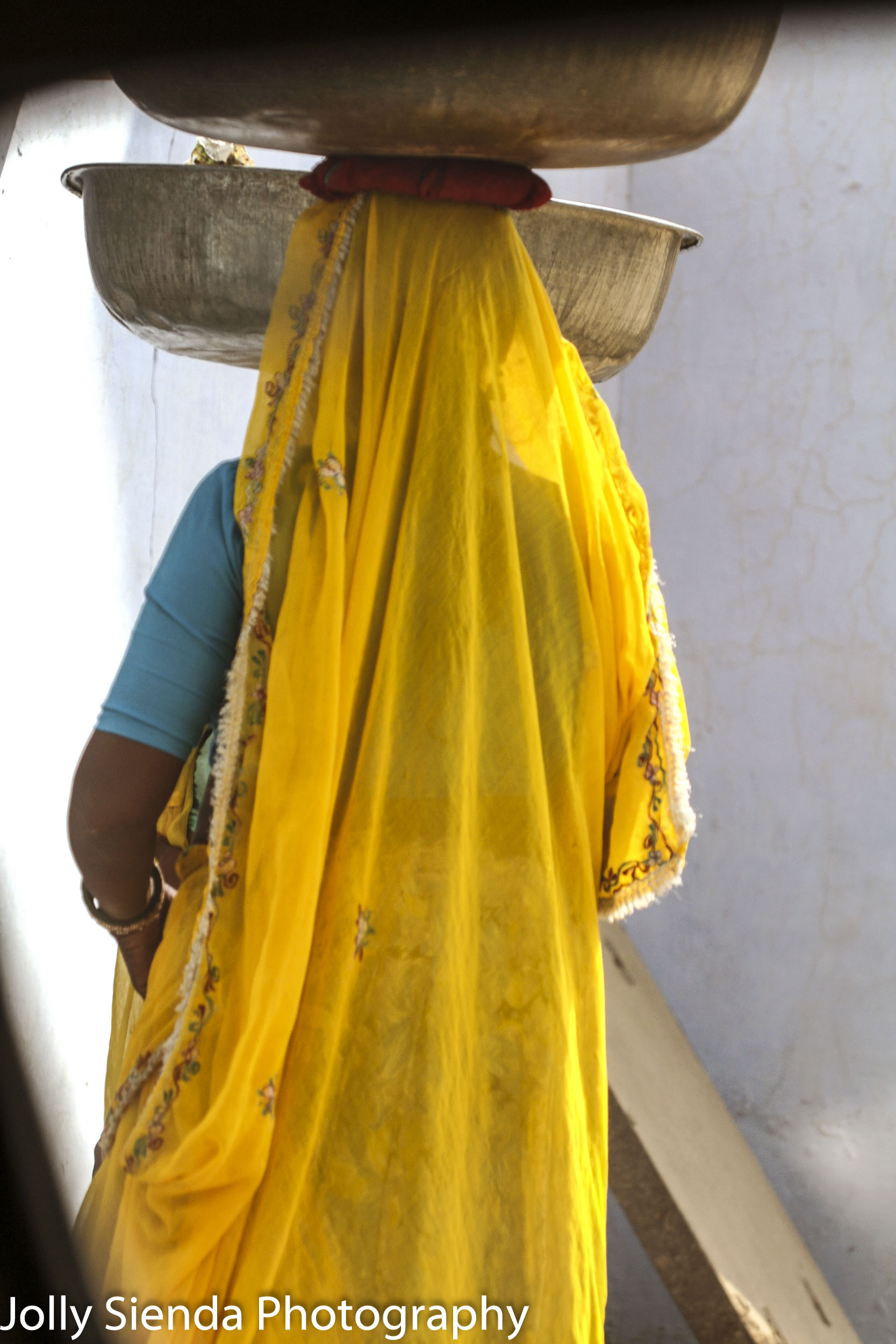 Woman wearing a sari balances copper bowls on her head