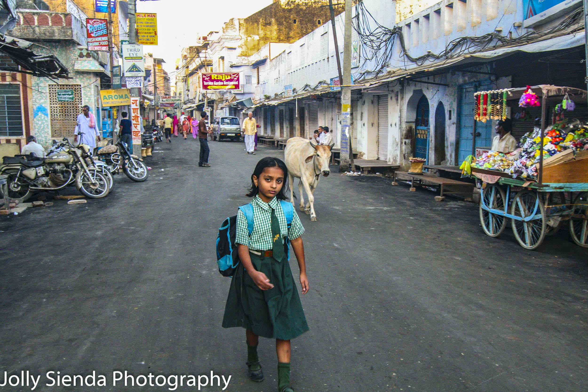 School girl in uniform walks down market street with a horned co
