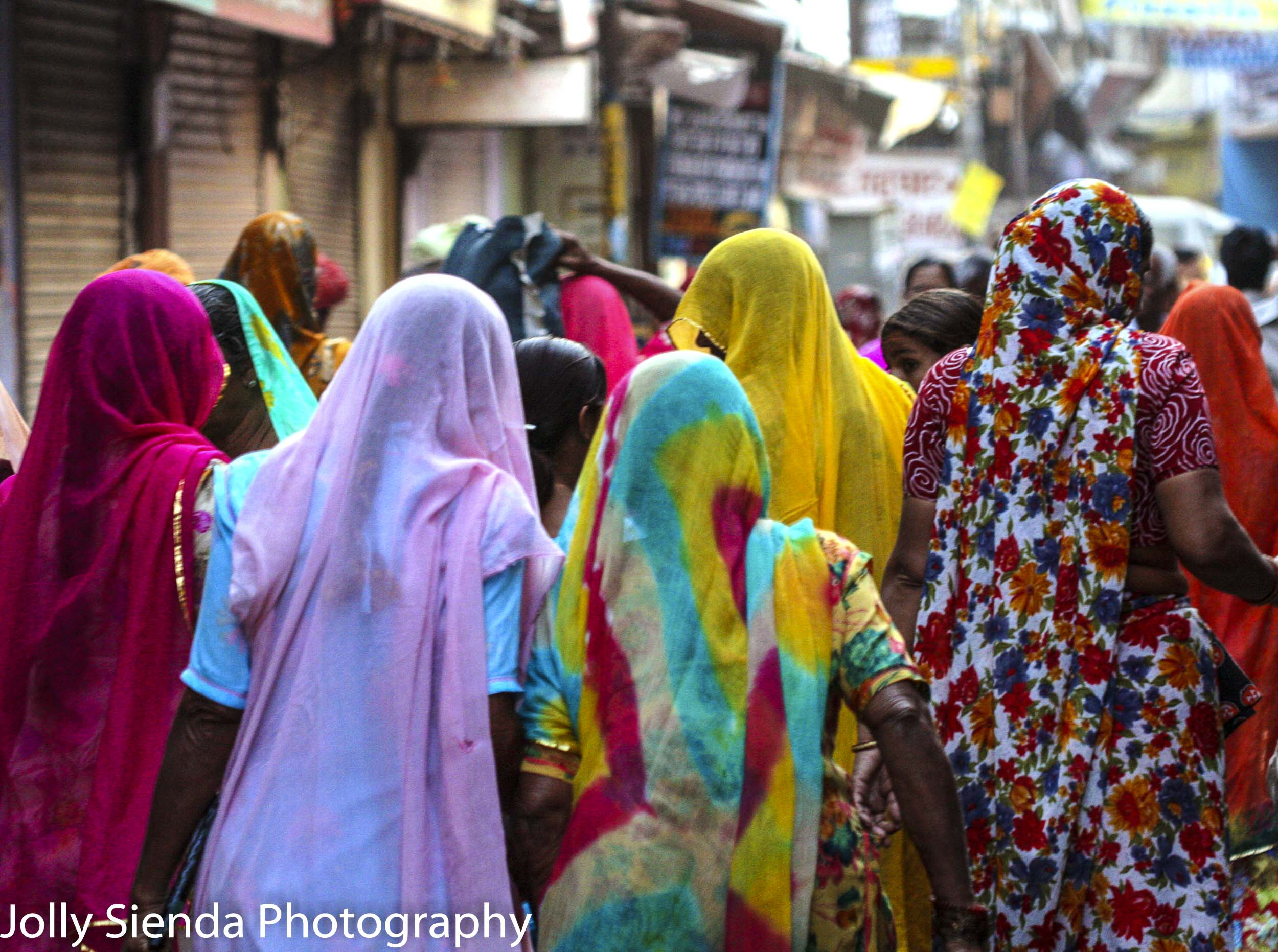 Crowd of women wearing colorful sari's walking in the market