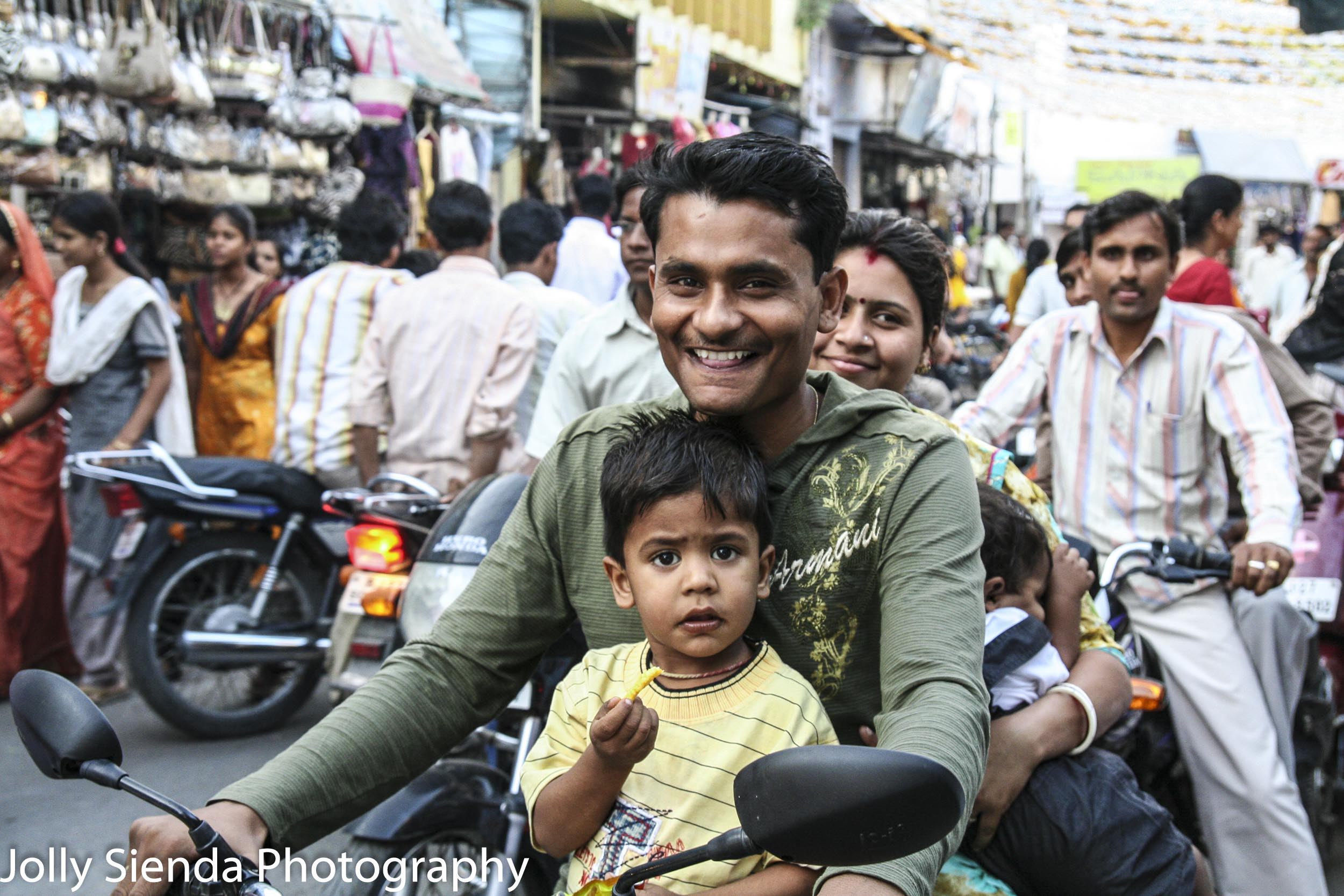 Family of four gets around the crowded market on a motorcyle