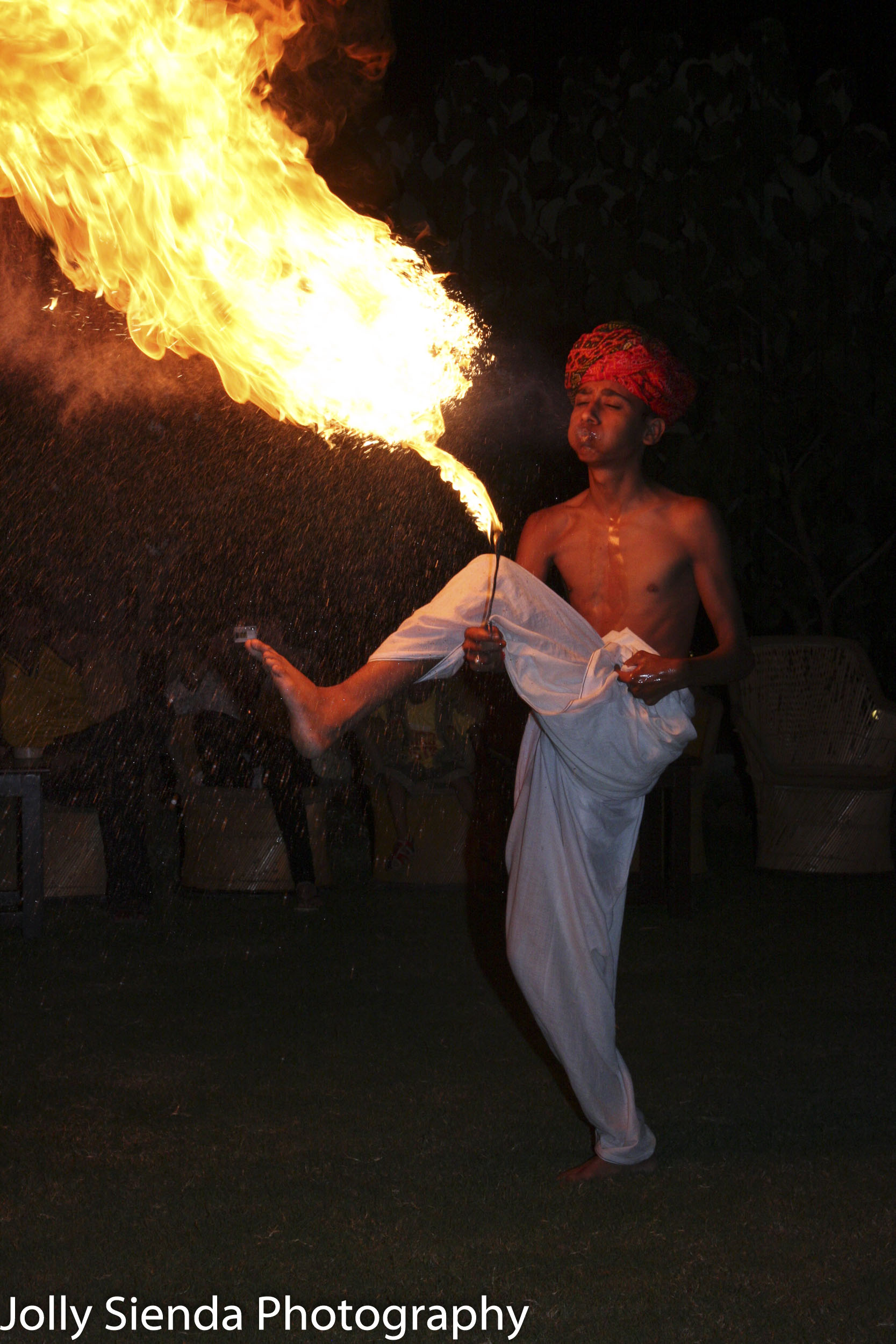 Man in the turban performing a dance with a large fire flame