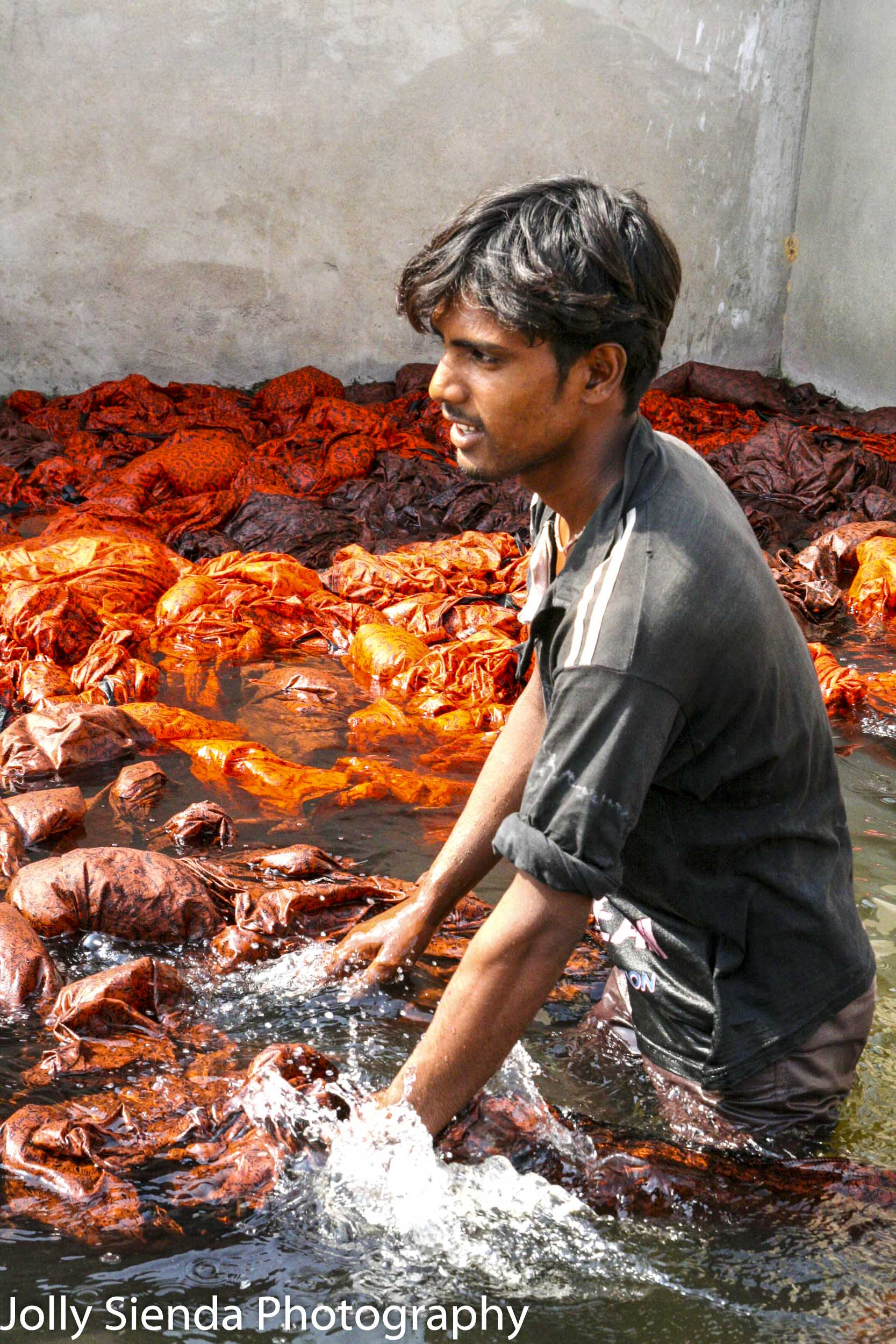 Young man wades in water working dyed block cotton cloth at a fa