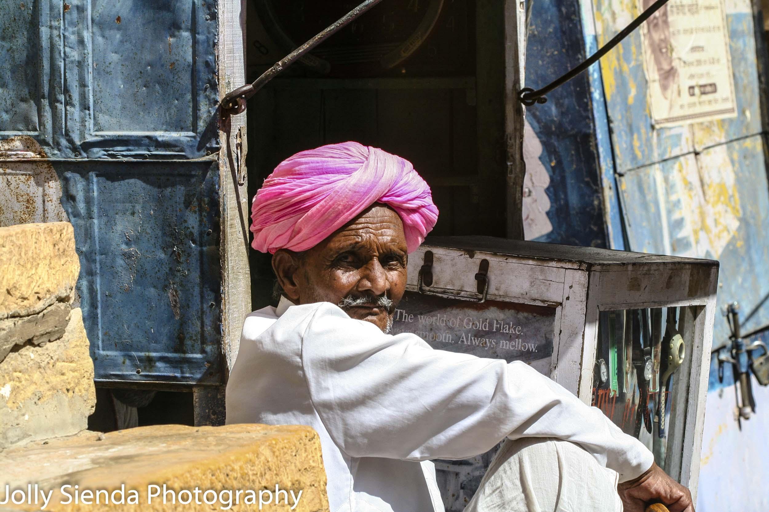 Man sitting wearing a pink turban