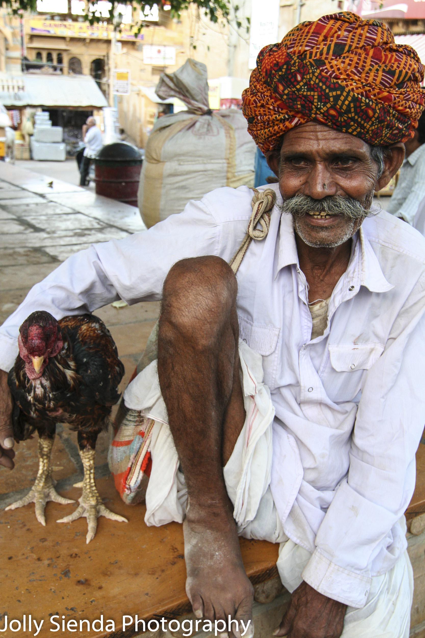 Chicken man wears a turban with his arm around his chicken