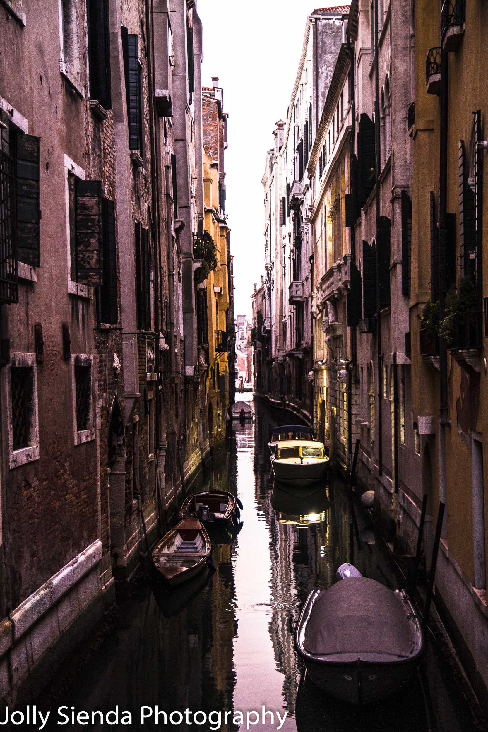Narrow Venetian canal and boats at sunrise