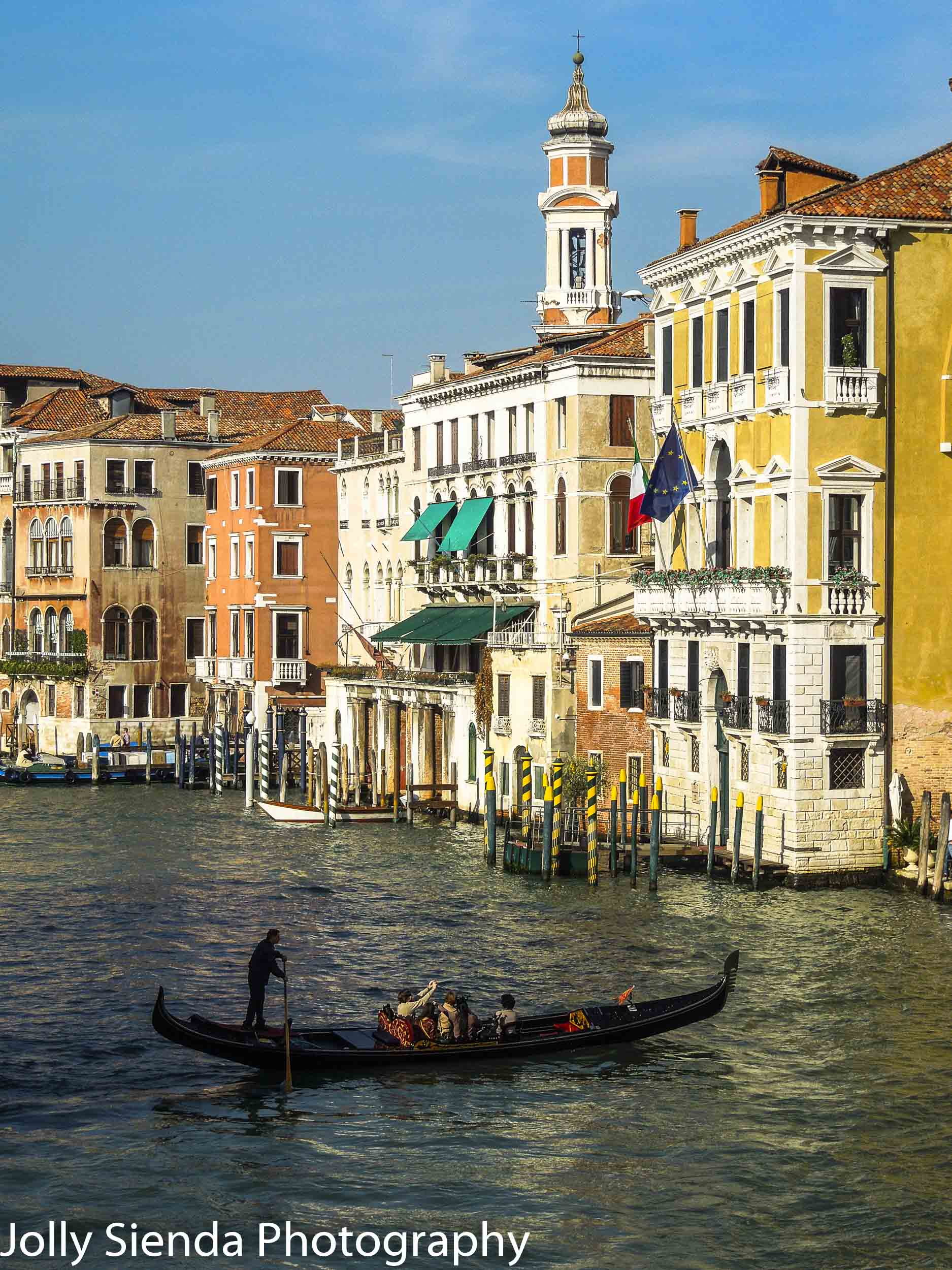 Gondolier uses his paddle to steer the gondola with tourists thr
