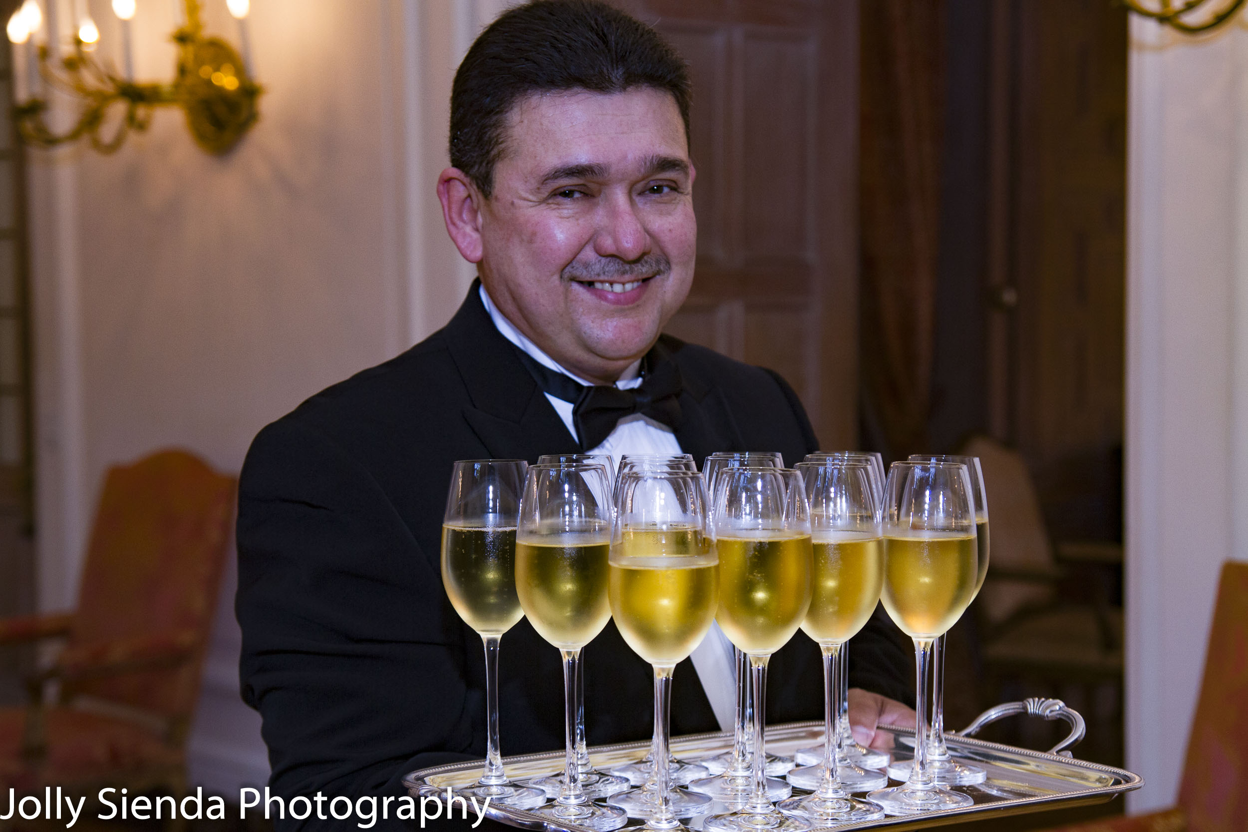 Smiling waiter carries wine glasses, French Ambassadors Dinner