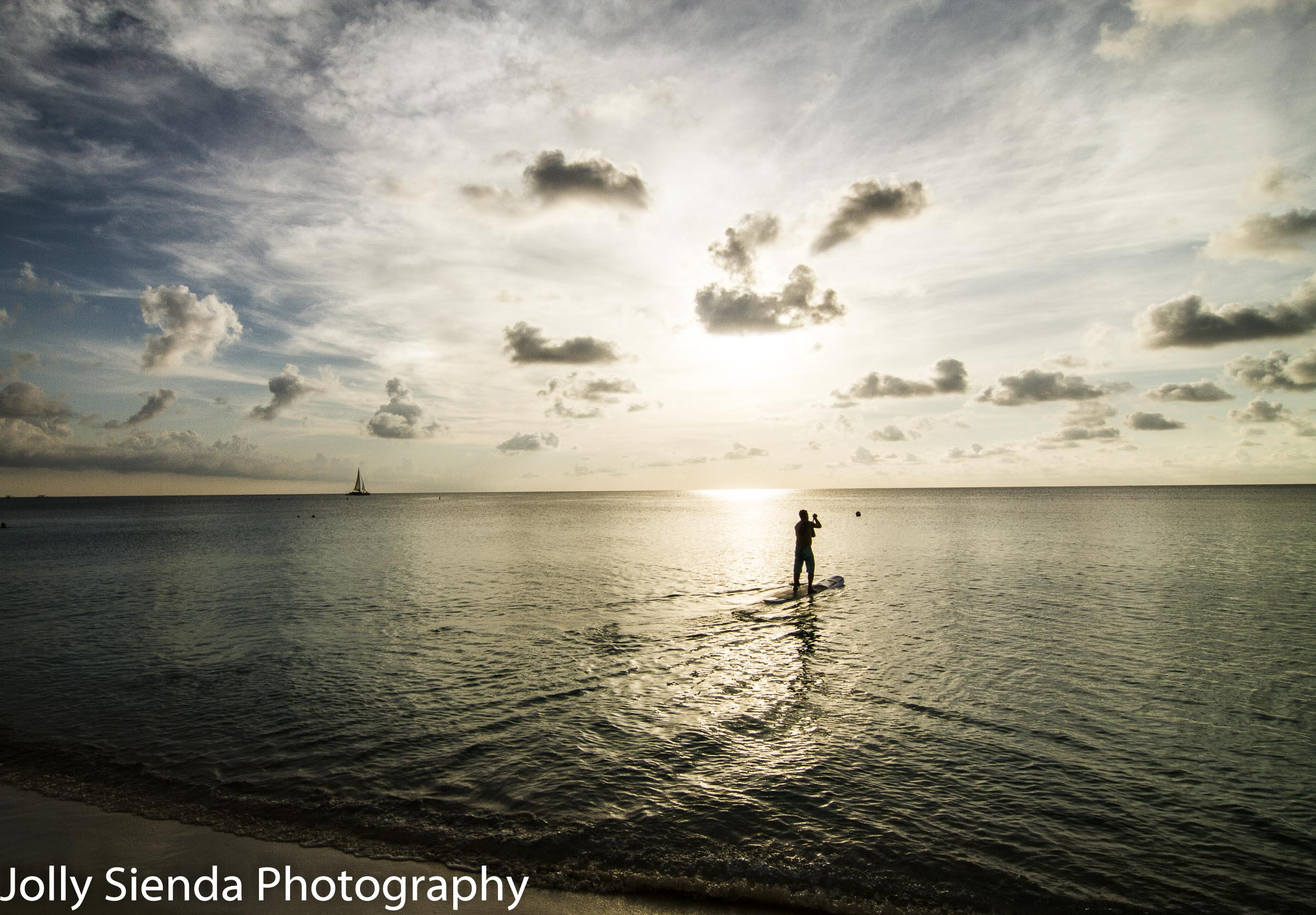 Paddle boarder rows out on the ocean to the sunset