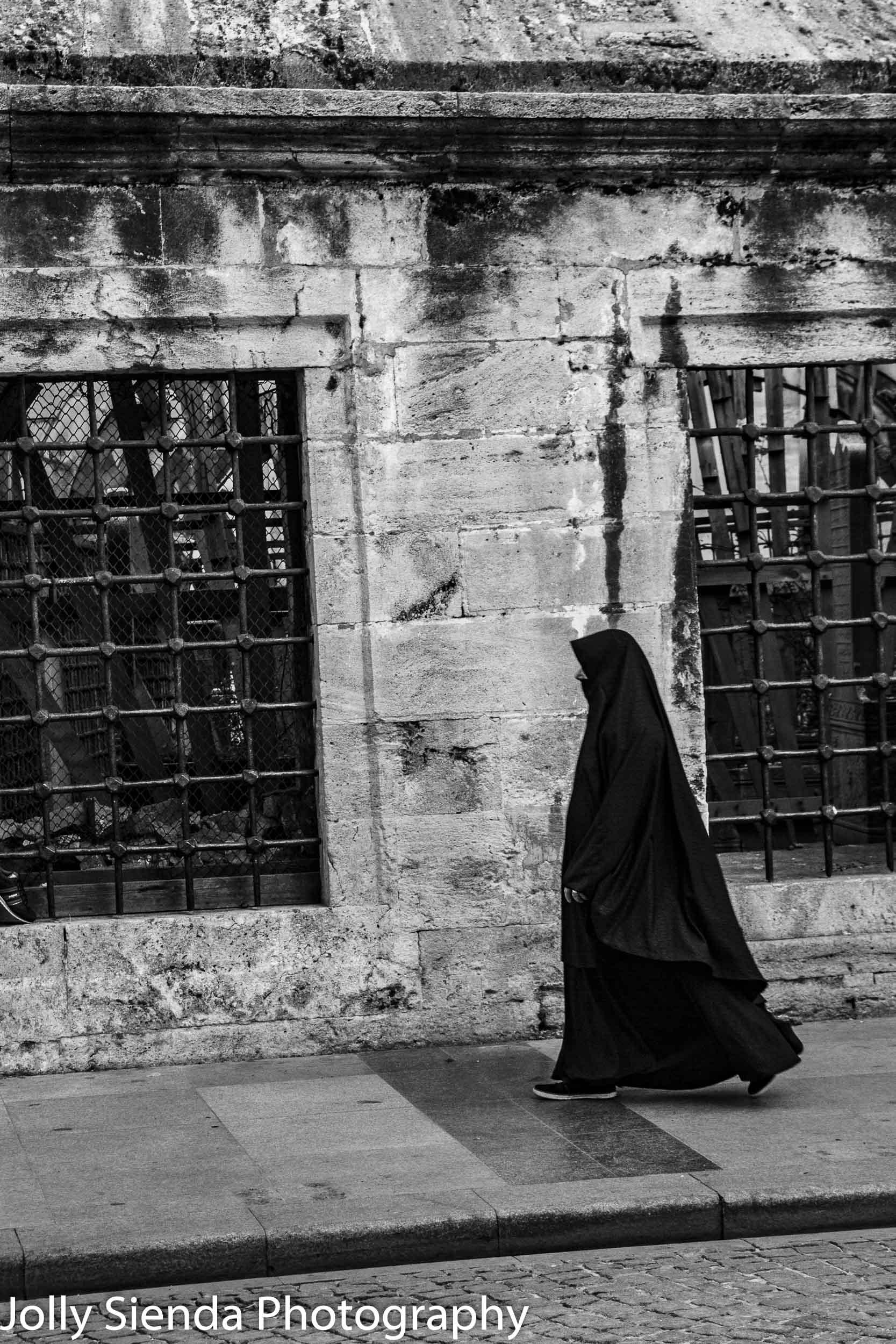 Woman walking on the street wearing a Hijab and Burqa