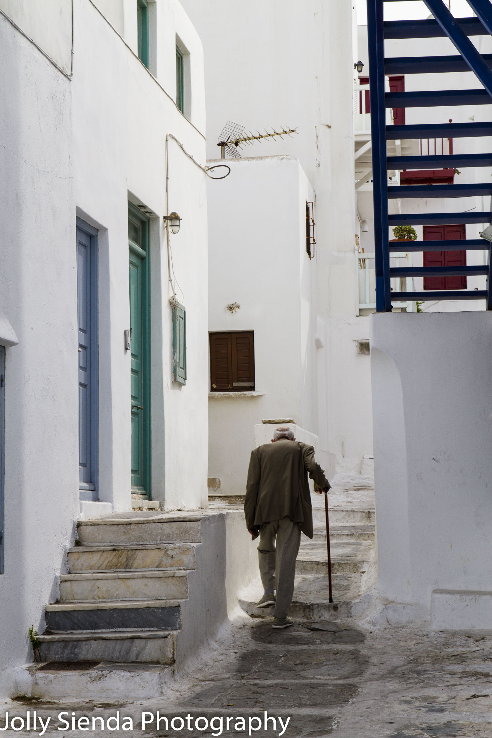 Elderly Man Walks with a Cane up Stucco Stairs in Mykonos