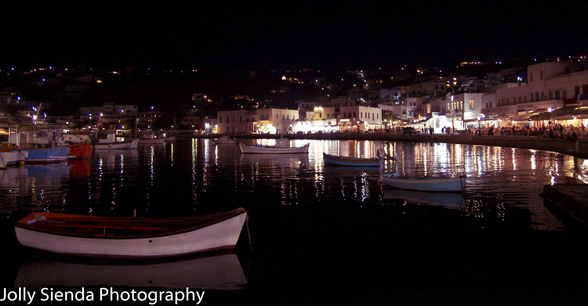 Boats and the town of Mykonos lit up at night