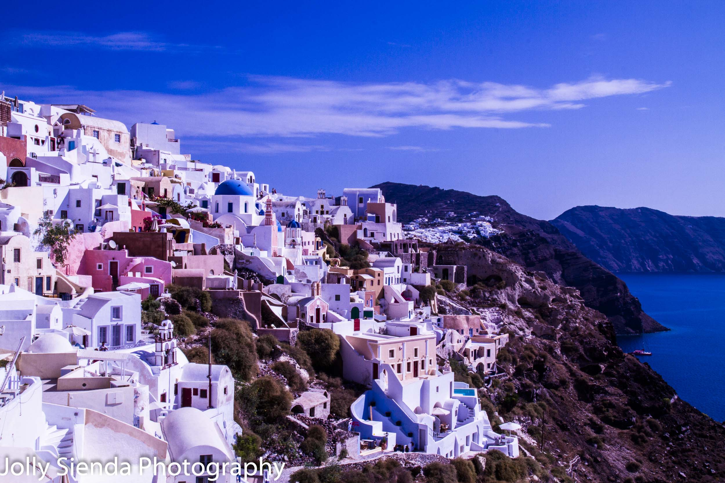 Oia, white washed and blue, sits over Caldera