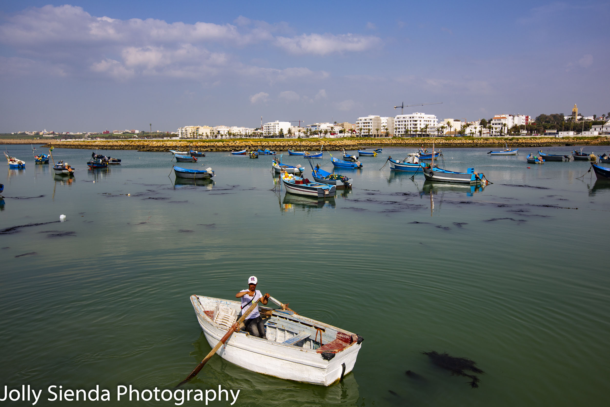 Fisherman and wooden blue boats