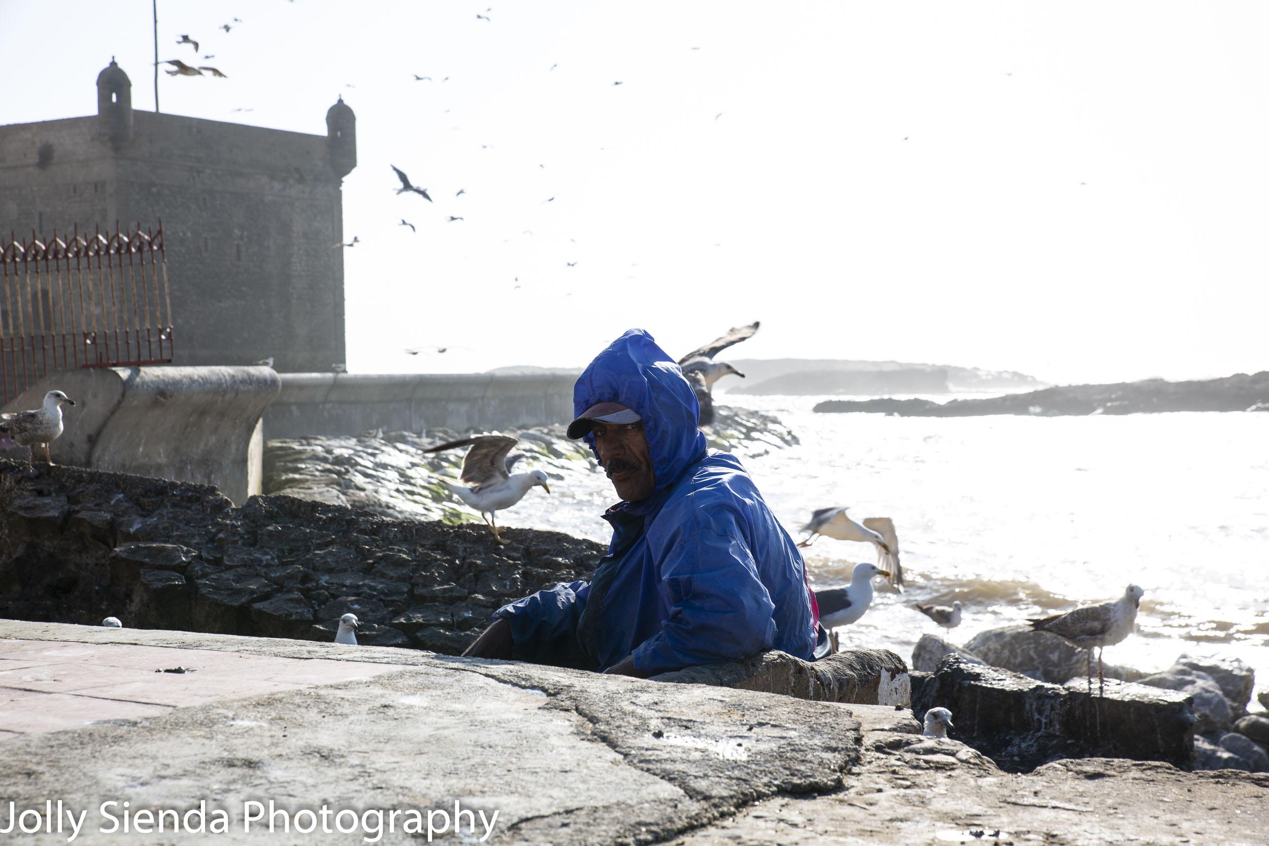 Fisherman wears blue raincoat at Essaouira fishing port