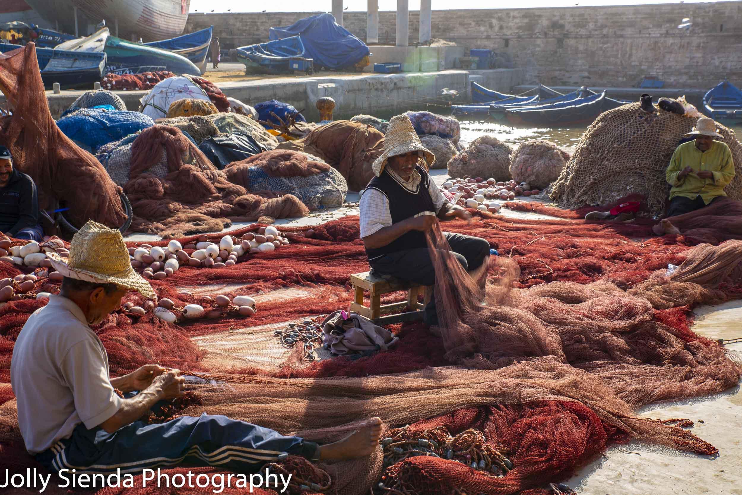 Fishermen repair fish nets
