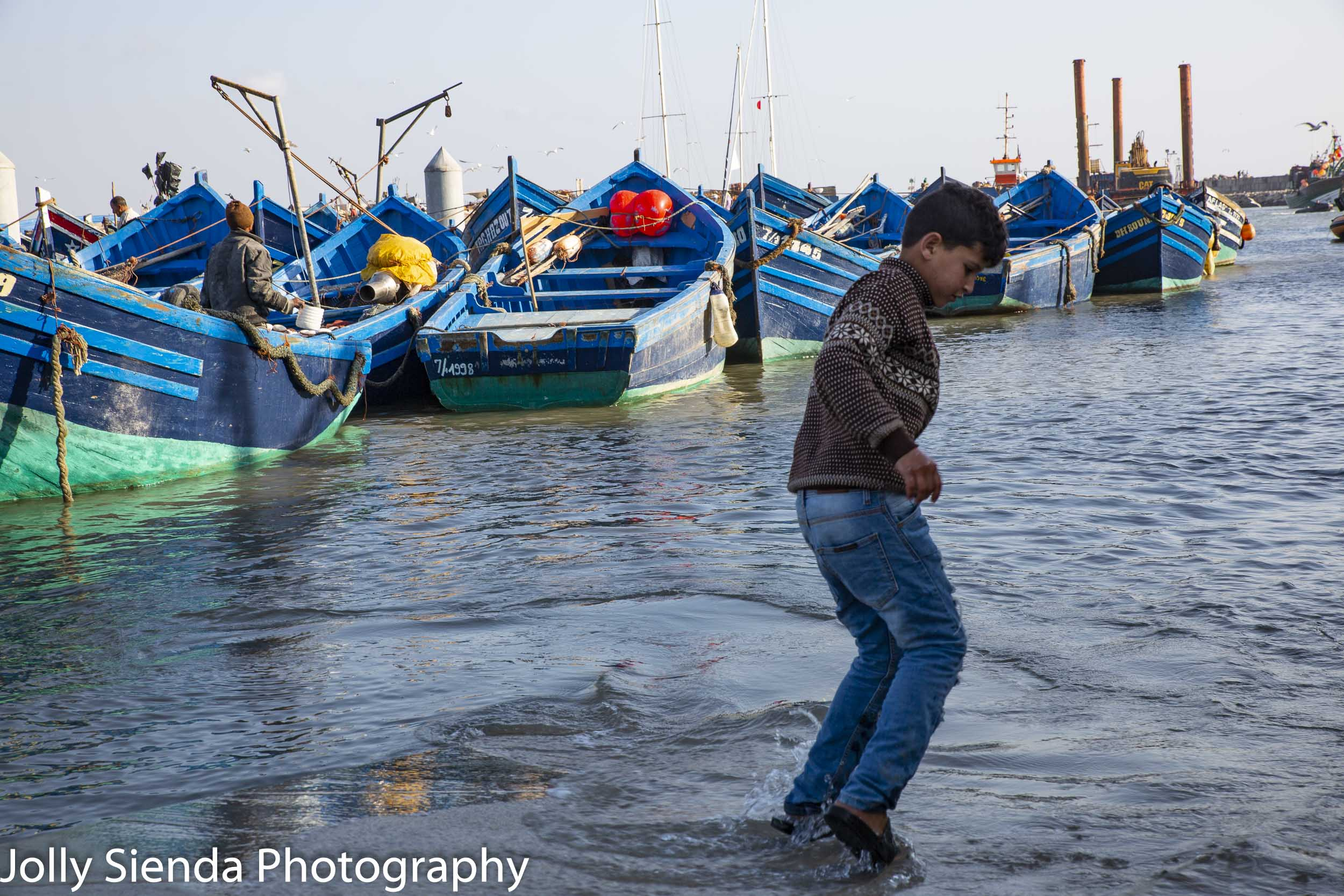 Boy plays in the water with fisherman and boats
